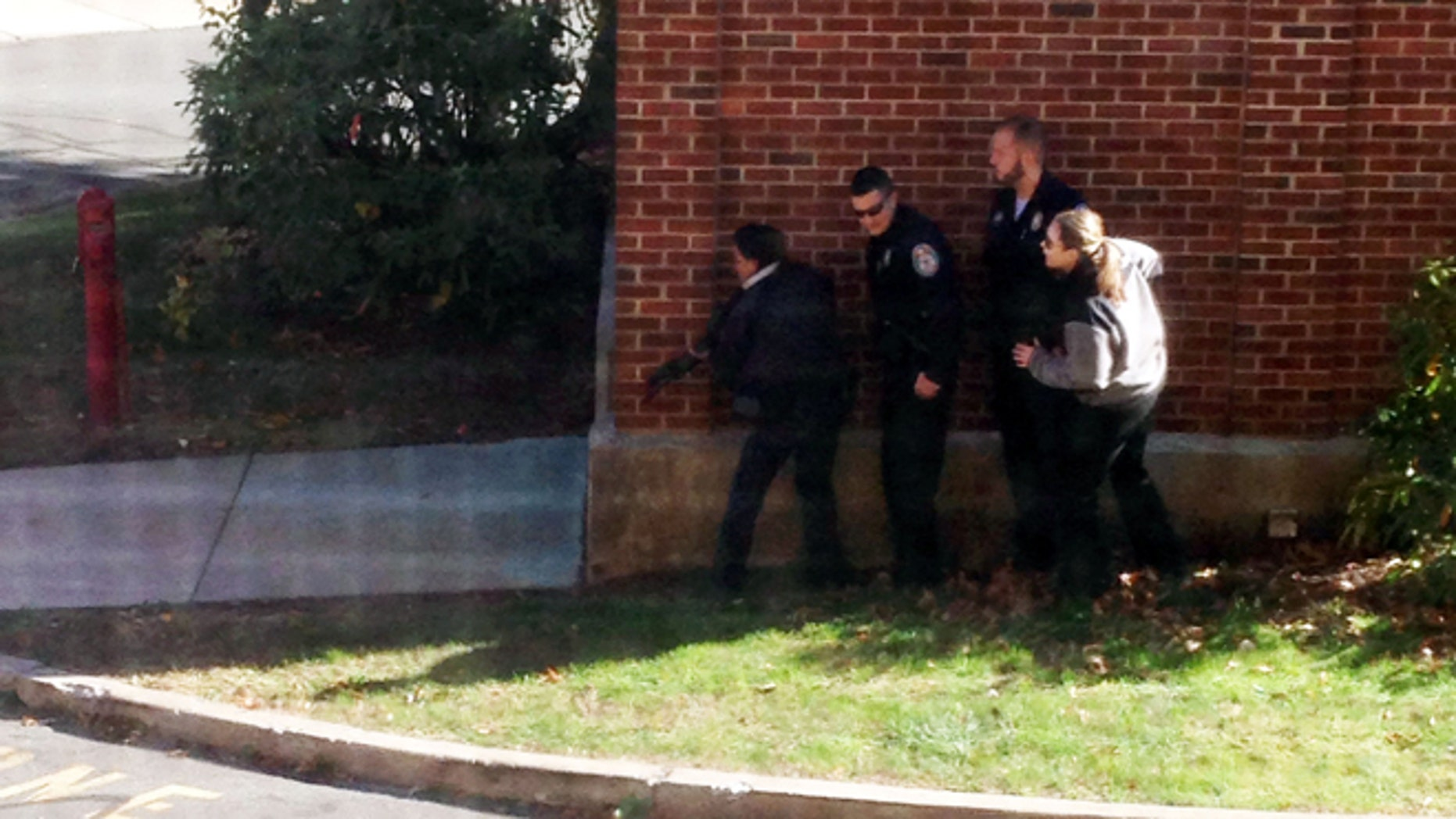 Nov. 4, 2013: In this photo taken through a window and provided to the AP, which has been authenticated based on its contents and other AP reporting, police officers respond  to a report of a suspicious person at Central Connecticut State University in  New Britain, Conn.