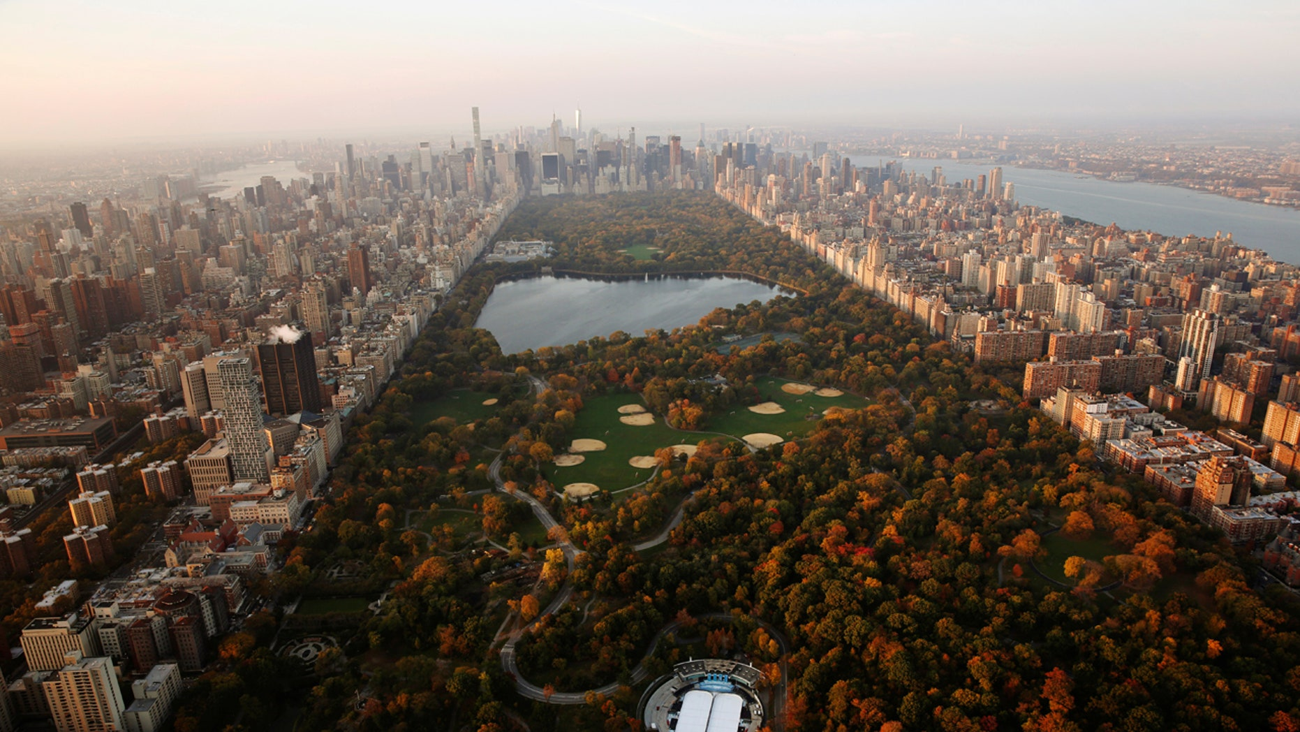 The rising sun lights trees in Central Park above the southern portion of the Manhattan borough of New York, U.S., November 2, 2016. REUTERS/Lucas Jackson  - RTX2RJZ7