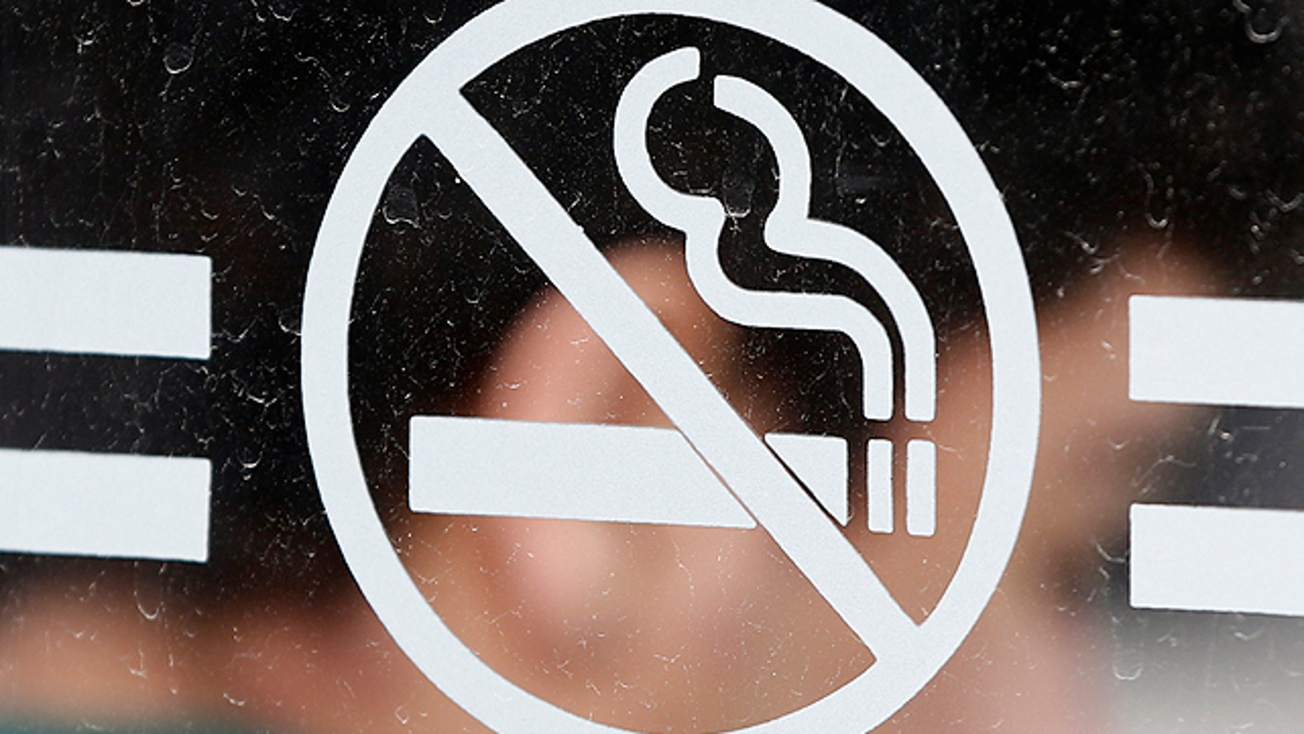 June 26, 2012: A student waits for a bus behind a no smoking sign at the State University of New York at Albany in Albany, N.Y. As tobacco bans are sweeping campuses nationwide, one California city has passed an ordinance requiring all apartments and condo units to be designated either smoking or non-smoking. (AP)