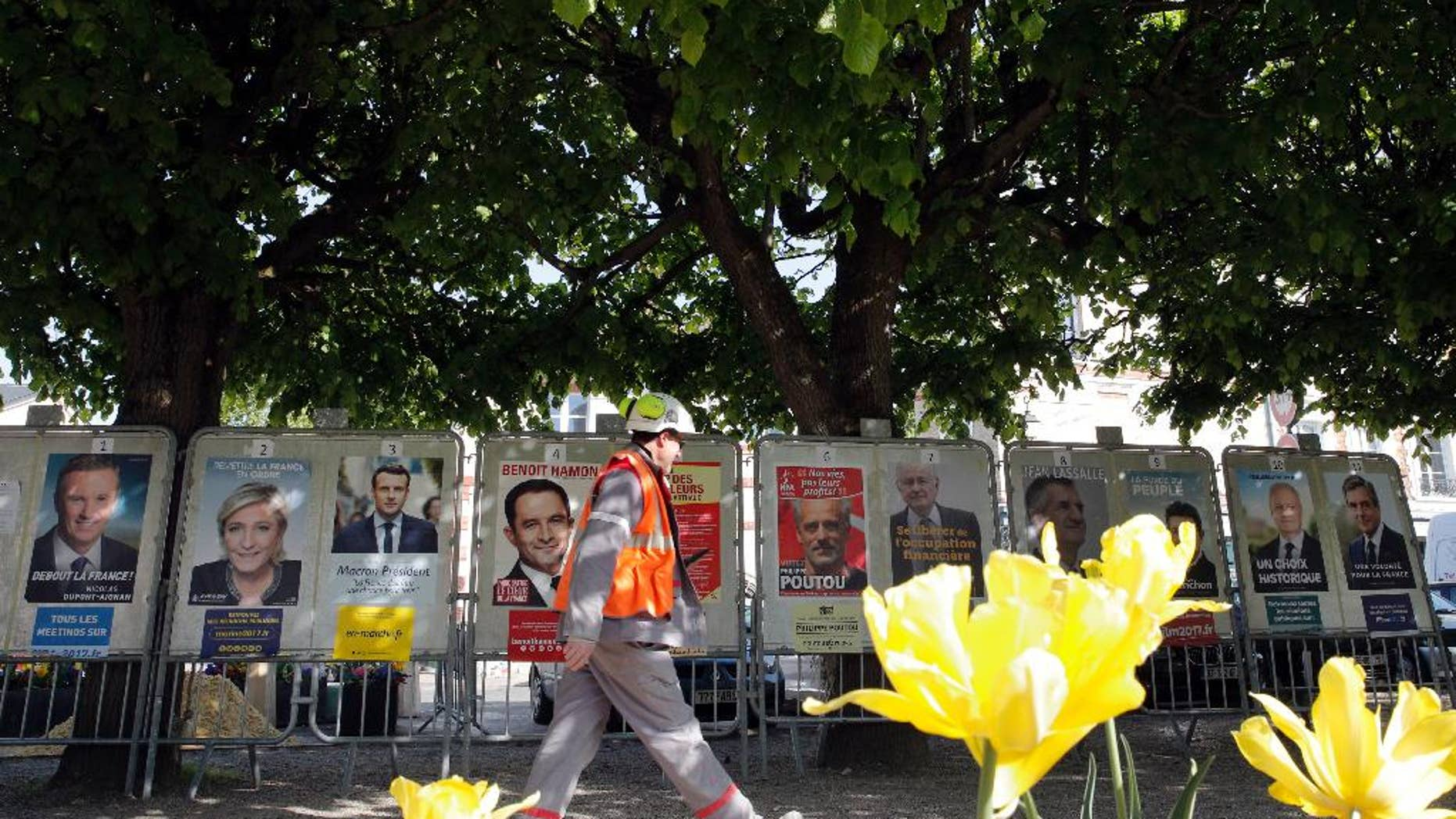 A man walks past French presidential campaign posters displayed in Marnes-la-Coquette, outside Paris, Thursday, April 20, 2017. The two-round presidential election is set for April 23 and May 7. (AP Photo/Christophe Ena)