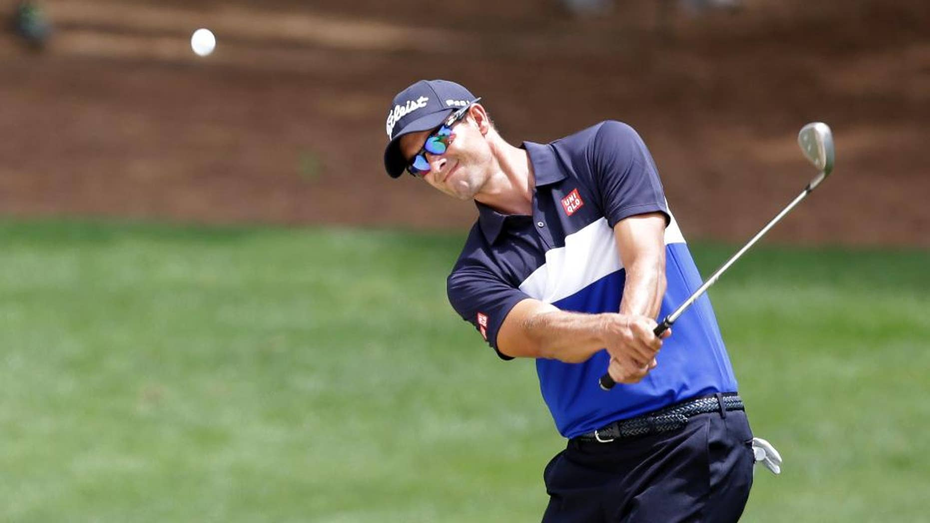 Adam Scott, of Australia, chips to the fourth green during the first round of the Wells Fargo Championship golf tournament at Quail Hollow Club in Charlotte, N.C., Thursday, May 14, 2015. (AP Photo/Bob Leverone)