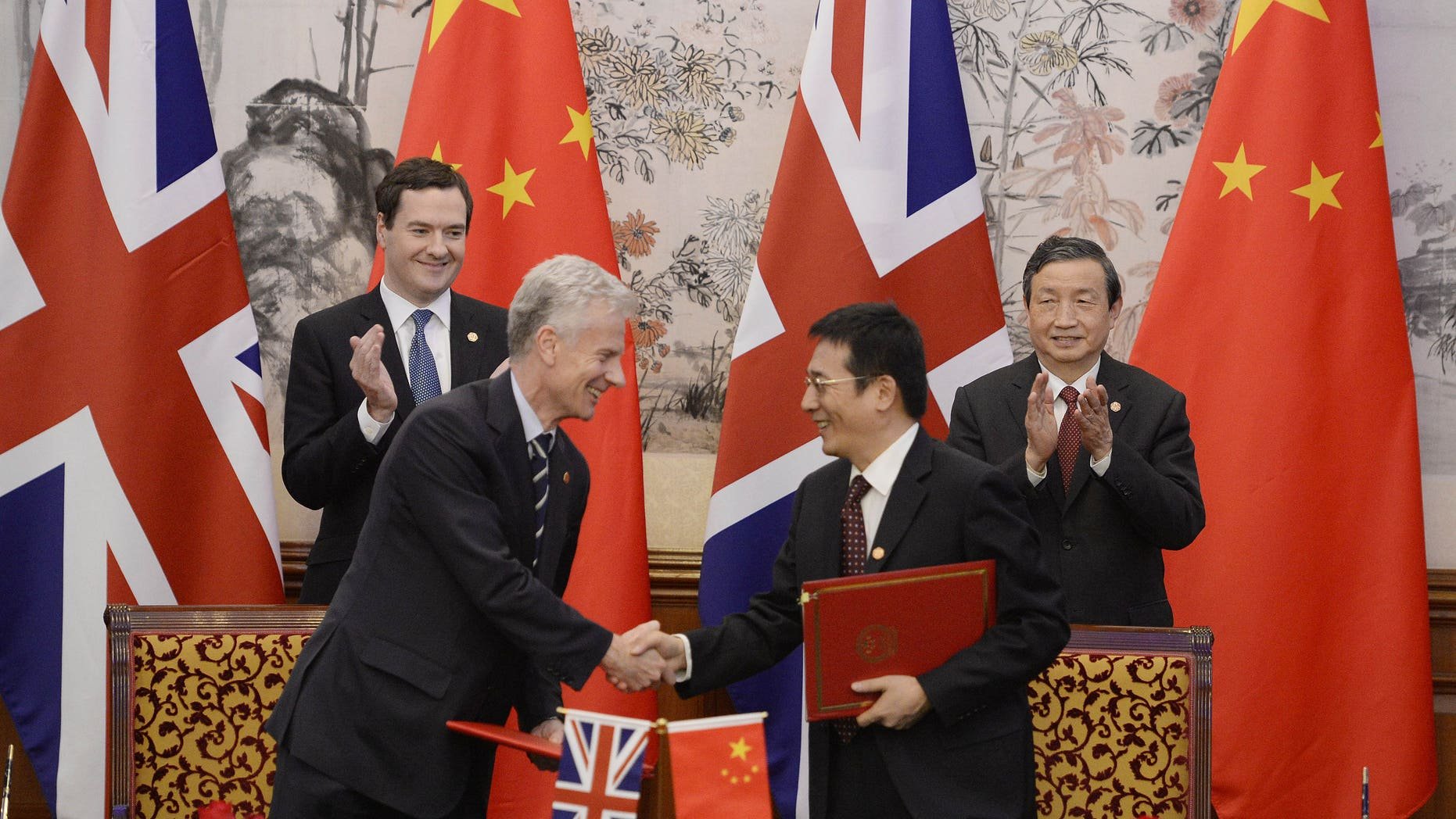 Britain's Chancellor of the Exchequer George Osborne, left, and Chinese Vice premier Ma Kai applaud as their officials shake hands after exchanging signed documents of their agreement during a signing ceremony at the Diaoyutai Guesthouse in Beijing Tuesday, Oct. 15, 2013. (AP Photo/Kota Endo, Pool)