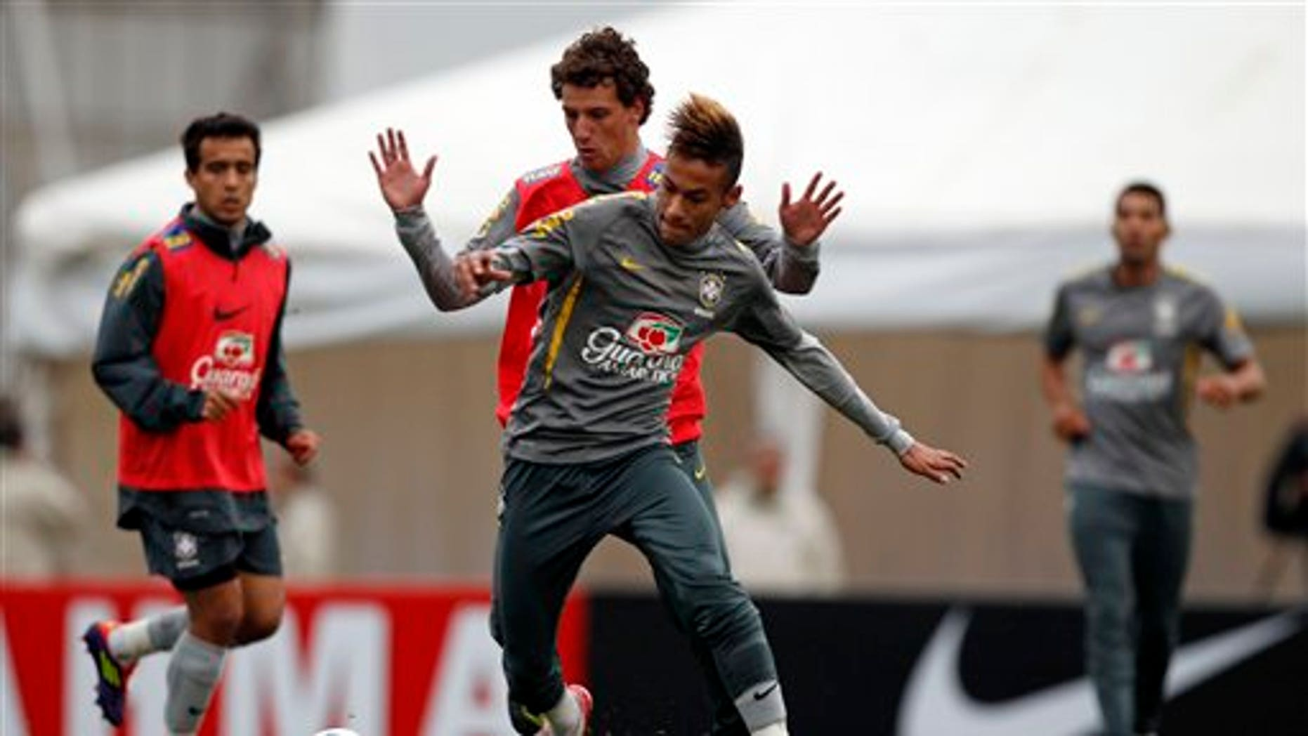July 15: Brazil's Elano and Neymar, fight for the ball during a training session near Campana, Argentina.