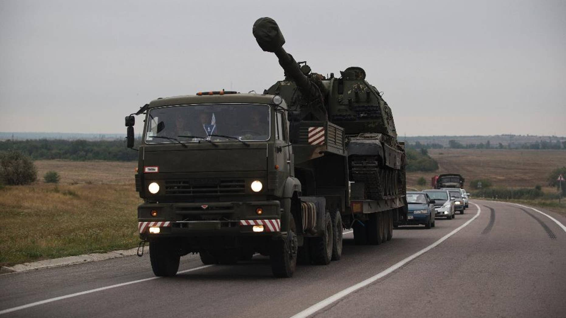 A Russian military truck carries a MSTA-S self-propelled howitzer about 10 kilometers from the Russia-Ukrainian border control point at town Donetsk, Rostov-on-Don region, Russia, Tuesday, Aug. 19, 2014. Ukrainian government troops were fighting pro-Russian rebels in the streets of Luhansk on Tuesday and captured most of a town near the eastern city of Donetsk, tightening the noose around that key rebel-held stronghold, Ukrainian officials said. (AP Photo/Pavel Golovkin)