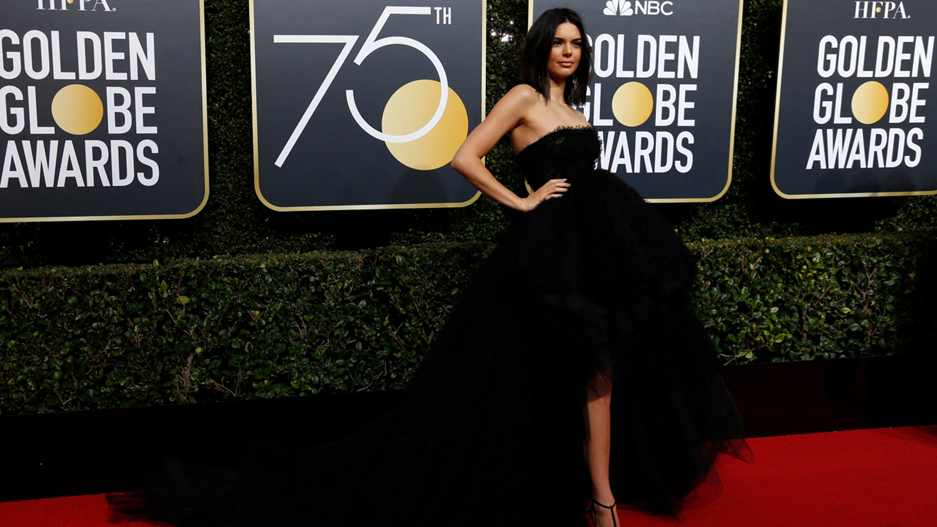The model posed on the Golden Globes red carpet in a strapless high-low ball gown paired with black Mary Jane heels.