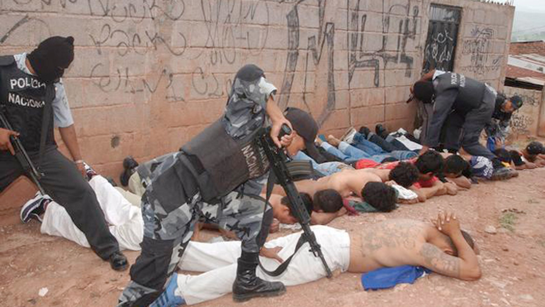 Police officers detain members of the Mara 18 and MS 13 gangs during the tour of President Ricardo Maduro and Security Minister Oscar Alvarez to the Colonia Bellavista neighborhood in Tegucigalpa, Honduras, Wednesday, July 2, 2003. The president sent a law to  Congress on Tuesday, prohibiting gangs in the country.(AP Photo/Antonio Romero)