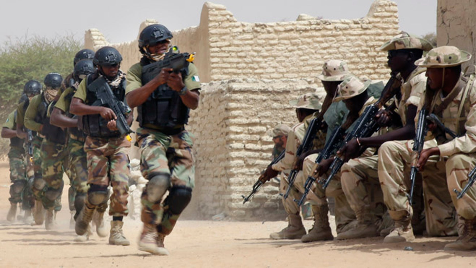 March 7, 2015: Nigerian special forces run past Chadian troops in an hostage rescue exercise at the end of the Flintlock exercise in Mao, Chad. The U.S. military and its Western partners conduct this training annually and set up plans long before Boko Haram began attacking its neighbors Niger, Chad and Cameroon.