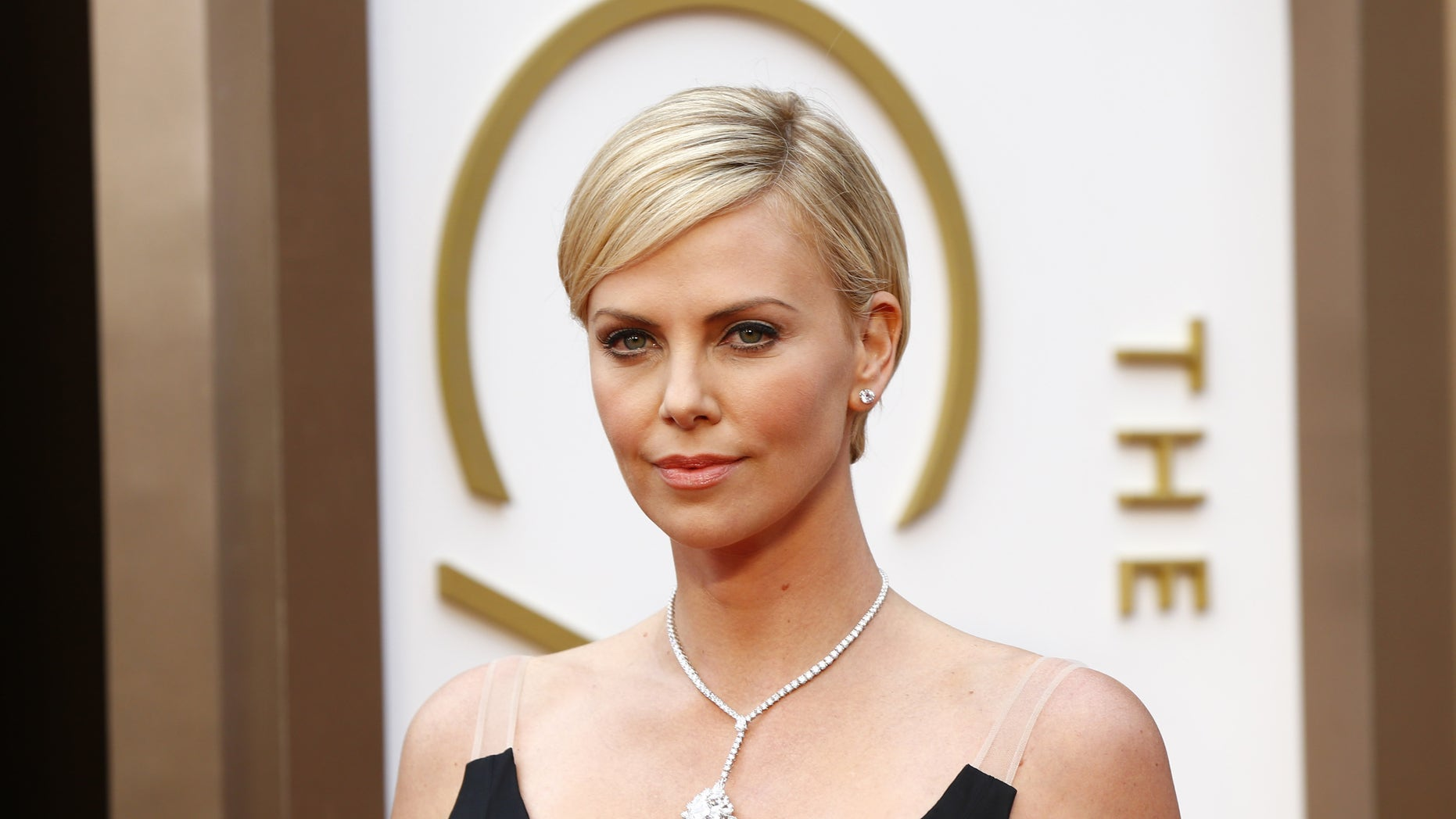 March 2, 2014. Actress Charlize Theron, in a black Dior gown and wearing $15 million worth of Harry Winston diamonds, arrives at the 86th Academy Awards in Hollywood, California.