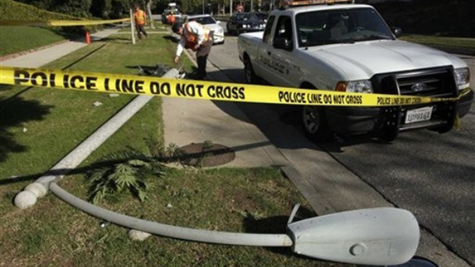 Nov. 16: A utility worker examines the site of the crash where Chasen was found inside her vehicle shot several times in the chest and killed, afterward crashing into this light pole (AP).