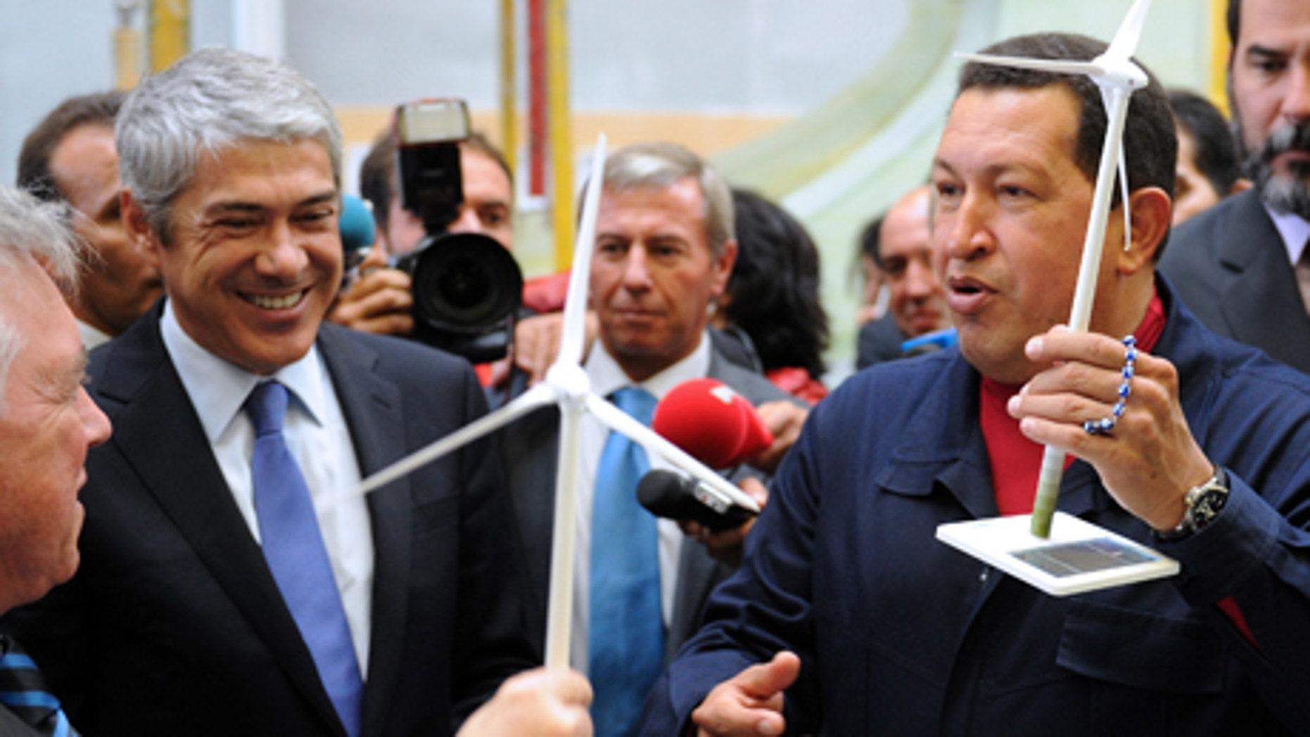 El presidente venezolano Hugo Chávez, derecha, y el primer ministro portugués José Sócrates reciben como regalo un aerogenerador en miniatura durante una visita a una fábrica de estos generadores de electricidad en el astillero Viana do Castelo, en Portugal, el domingo 24 de octubre del 2010. (AP foto/Paulo Duarte)