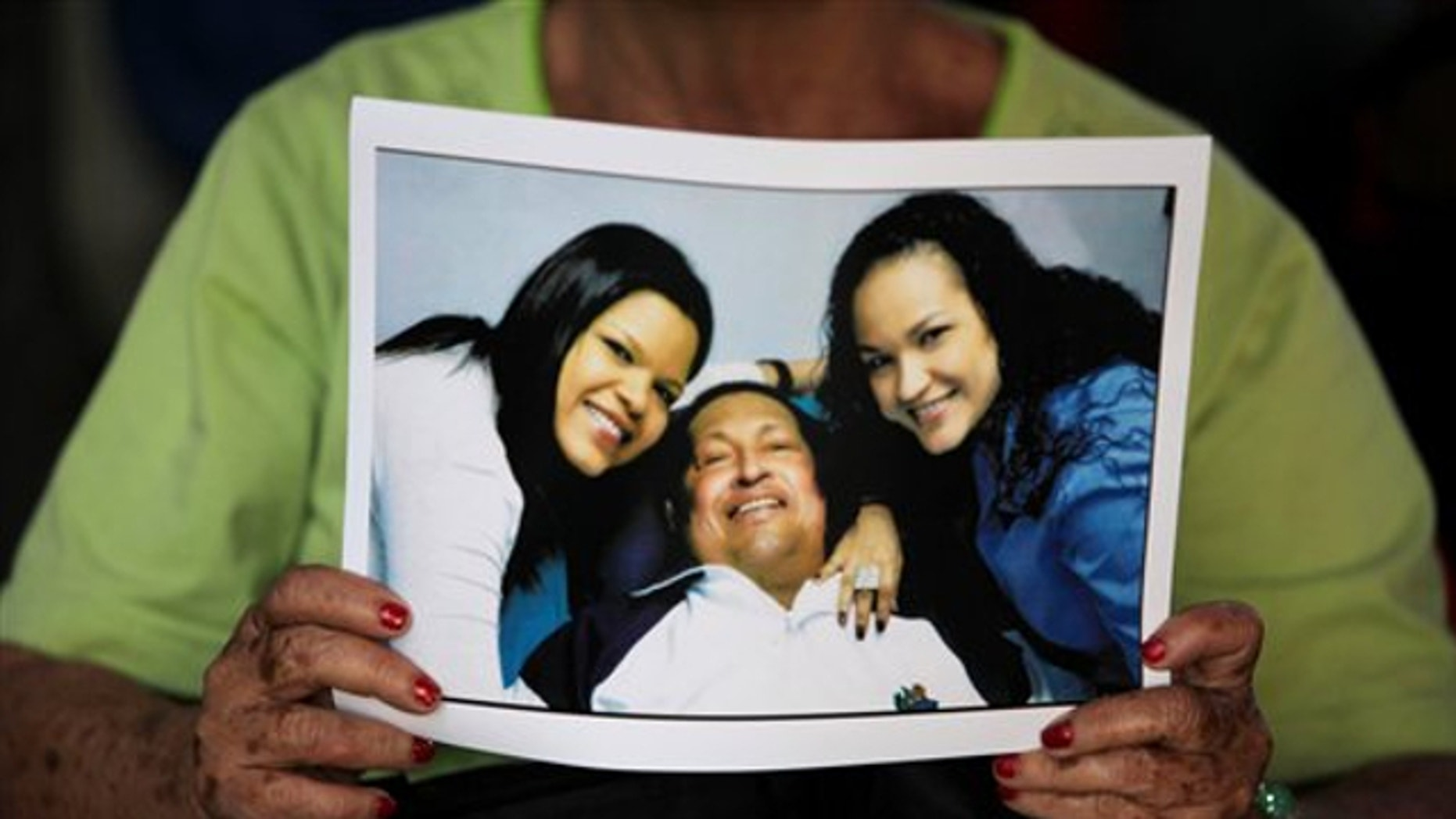 Feb. 15, 2013: A woman holds a newly purchased copy of a photo released by the government, showing Venezuela's President Hugo Chavez with two of his daughters, in Caracas,Venezuela.