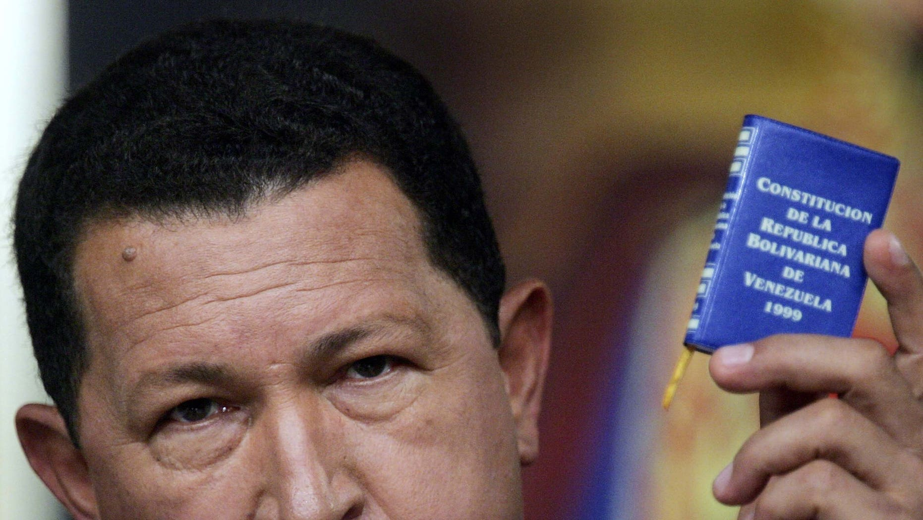 CARACAS, VENEZUELA - DECEMBER 05:  Venezuelan President Hugo Chavez speaks at a press conference while holding a copy of the Venezuelan constitution in Miraflores Palace December 5, 2006 in Caracas, Venezuela. Chavez was officially declared the re-elected president by electoral authorities today after defeating challenger Manuel Rosales in the December 3 election.  (Photo by Mario Tama/Getty Images)