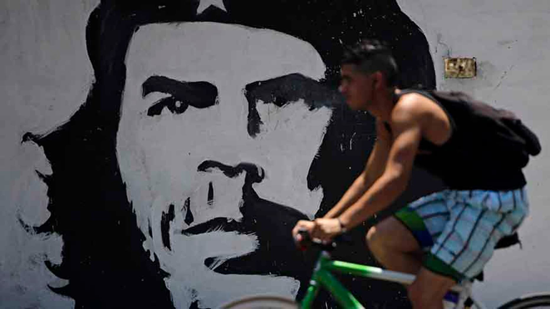A man cycles beside a mural with the image of Cuban revolution leader Che Guevara in Havana, Cuba.