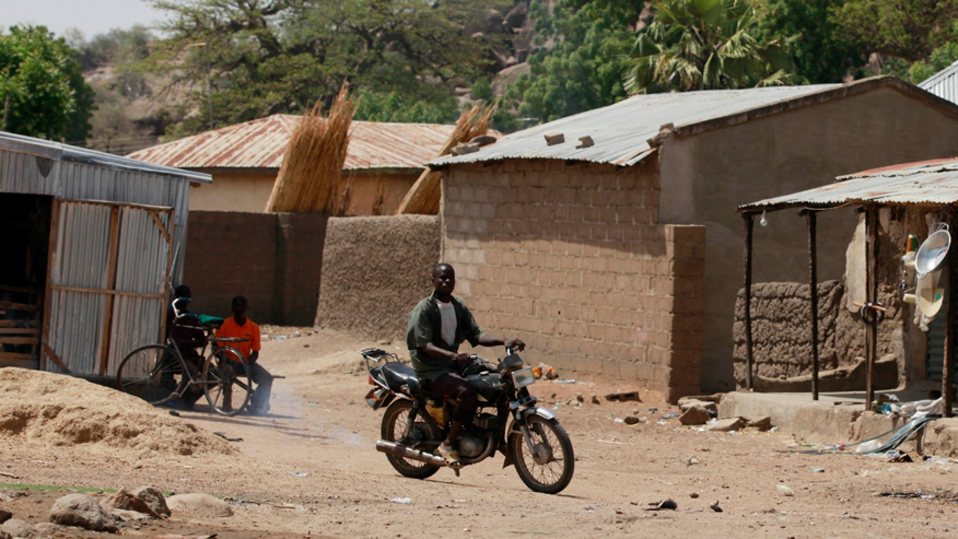 Jan. 28, 2016: An unidentified man rides a motorbike past houses in Chibok, Nigeria.