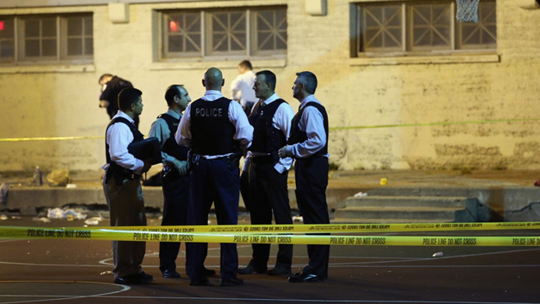 CHICAGO, IL - SEPTEMBER 19:  Police investigate the scene in Cornell Square Park on the Southside where 11 people including a three-year-old child were shot on September 19, 2013 in Chicago, Illinois. Eighteen people were reported shot in the city, including one fatally, in less than a four-hour period on Thursday evening.  (Photo by Scott Olson/Getty Images)