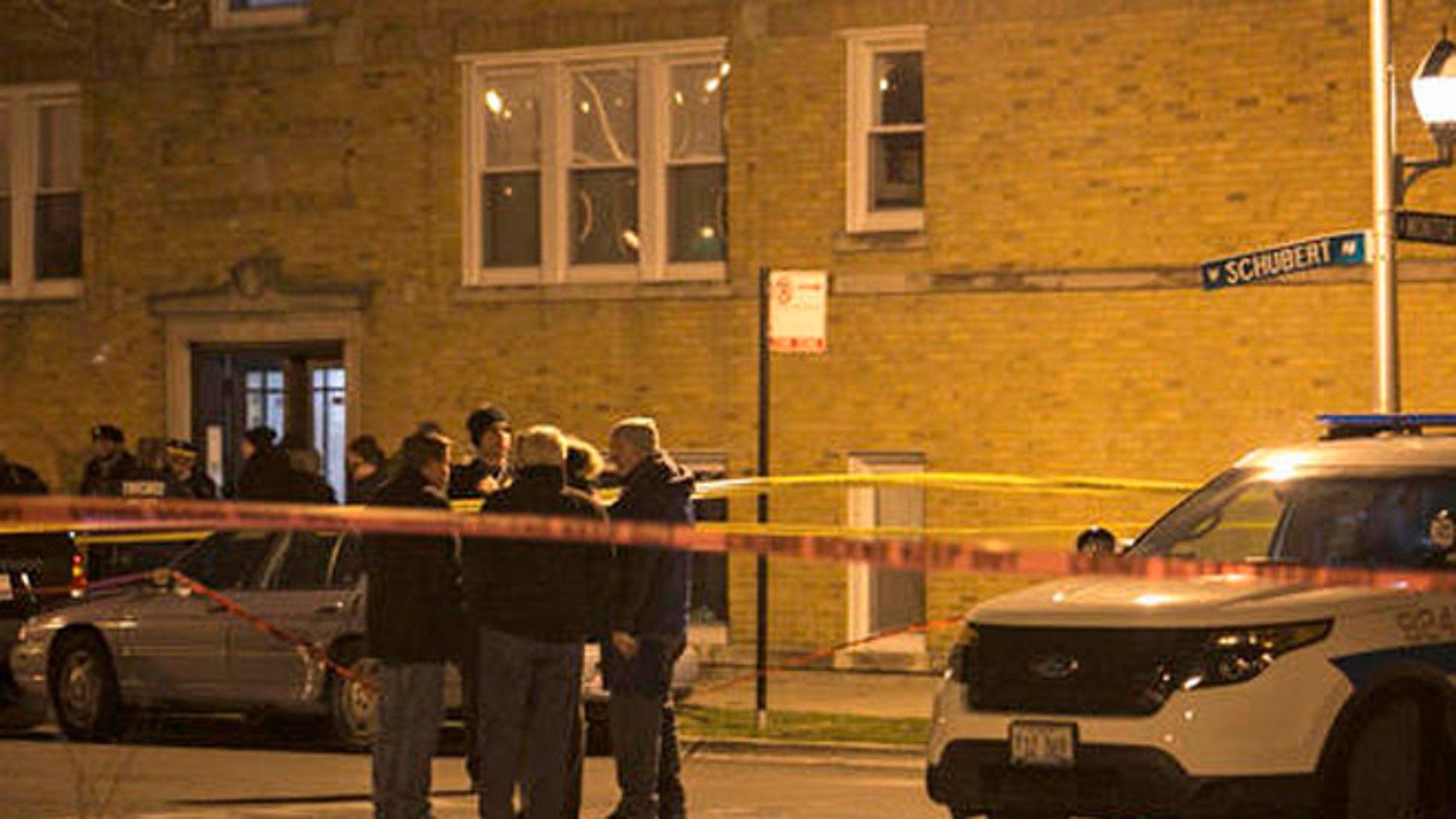 In this March 20, 2016 photo, Chicago Police investigate the scene where an off-duty police officer shot a bat-wielding man on the Northwest Side in Chicago.