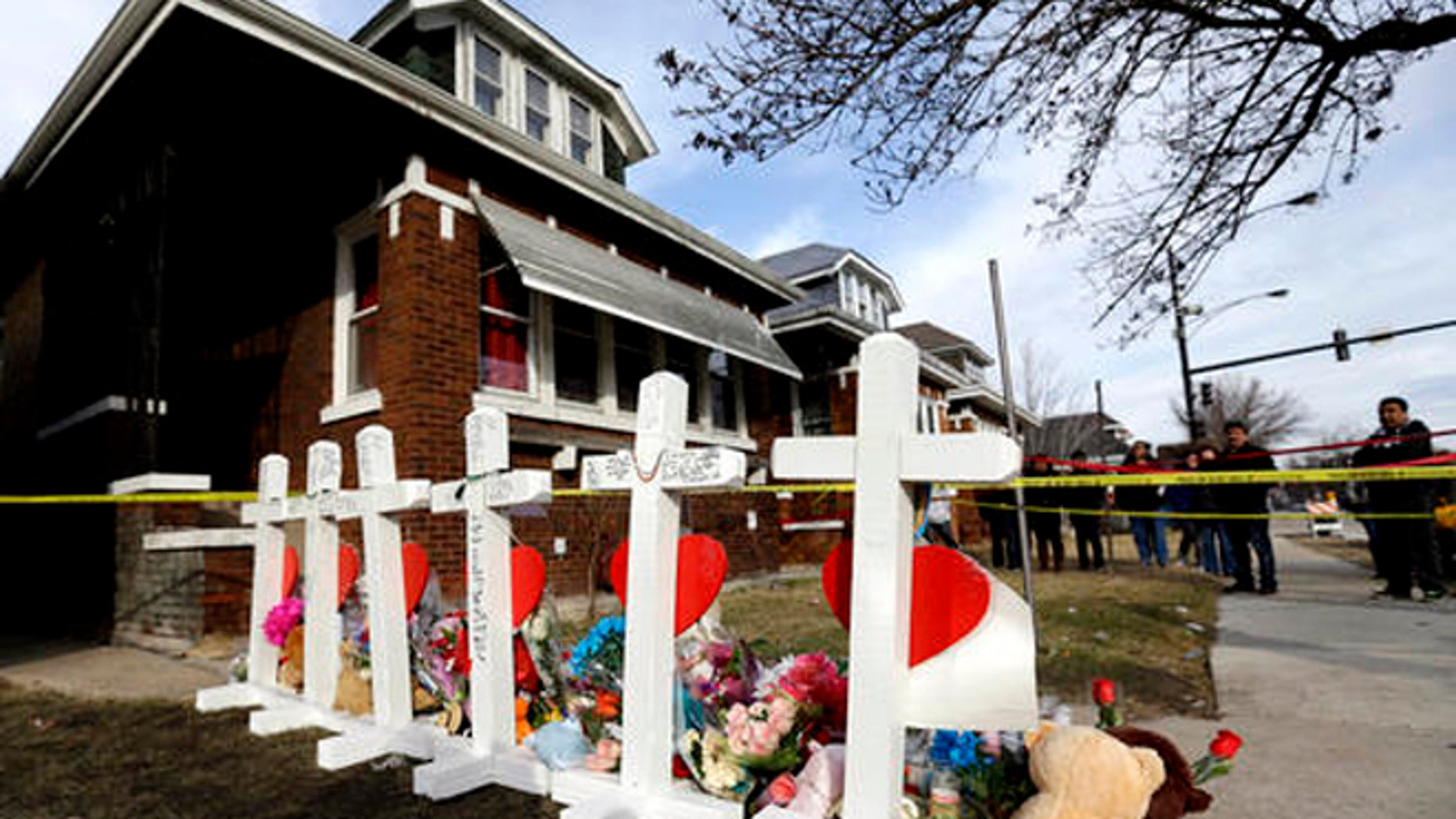 In this Feb. 7, 2016 file photo, mourners pay their respect outside a home in Chicago where six family members were found dead.