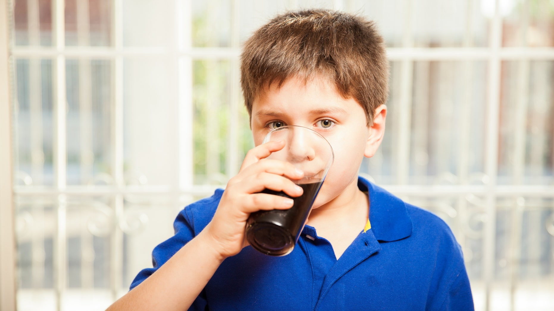 Portrait of a young boy drinking soda from a glass at home