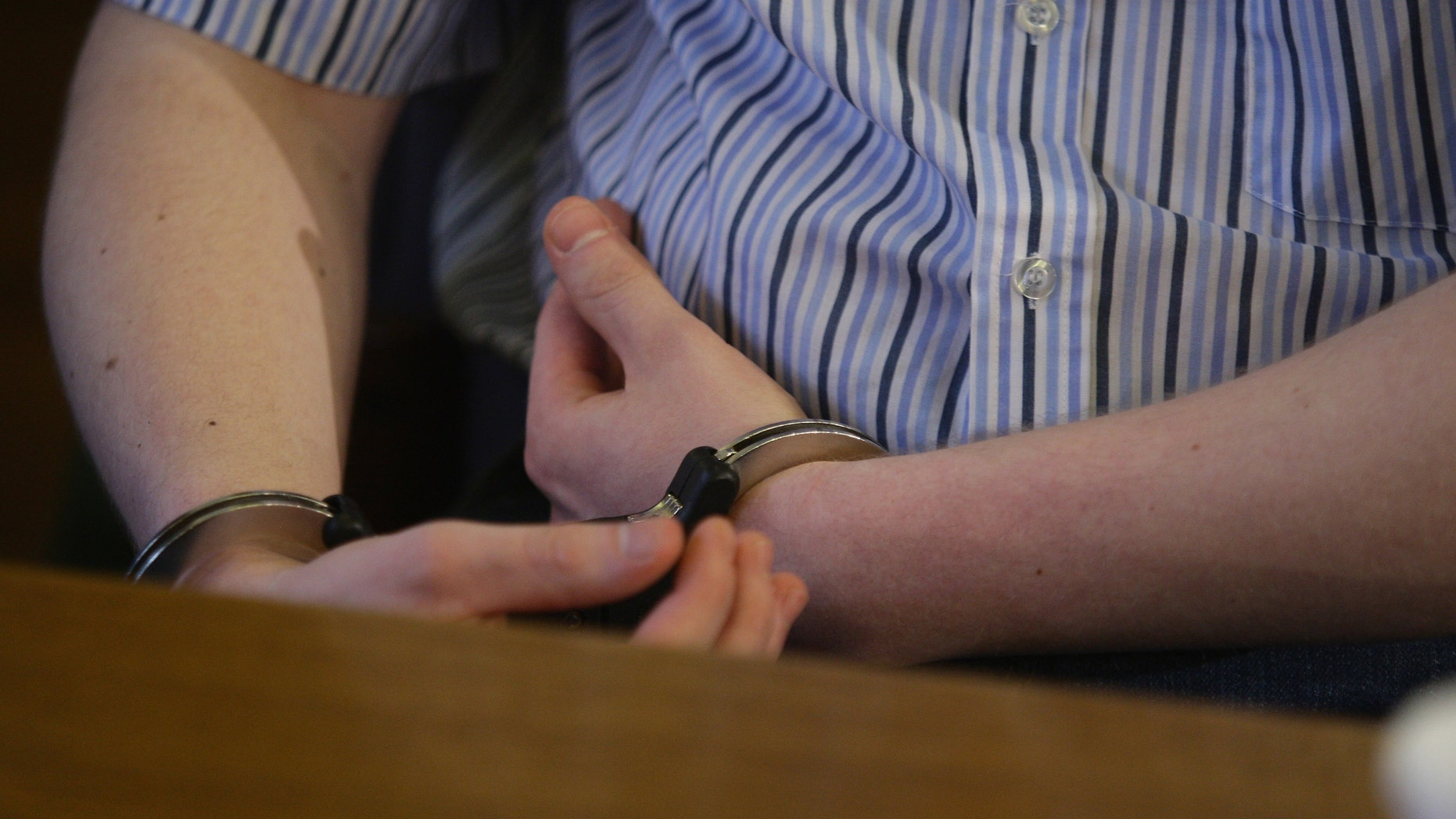 LEIPZIG, GERMANY - AUGUST 17:  The accused Daniel V. in handcuffs is seen at the Leipzig district court at the first day of the 'Michelle' trial on August 17, 2009 in Leipzig, Germany. Accused Daniel is suspect in the murder of the eight year old child Michelle, who was found dead in a Leipzig pond in September, 2008.  (Photo by Andreas Rentz/Getty Images)