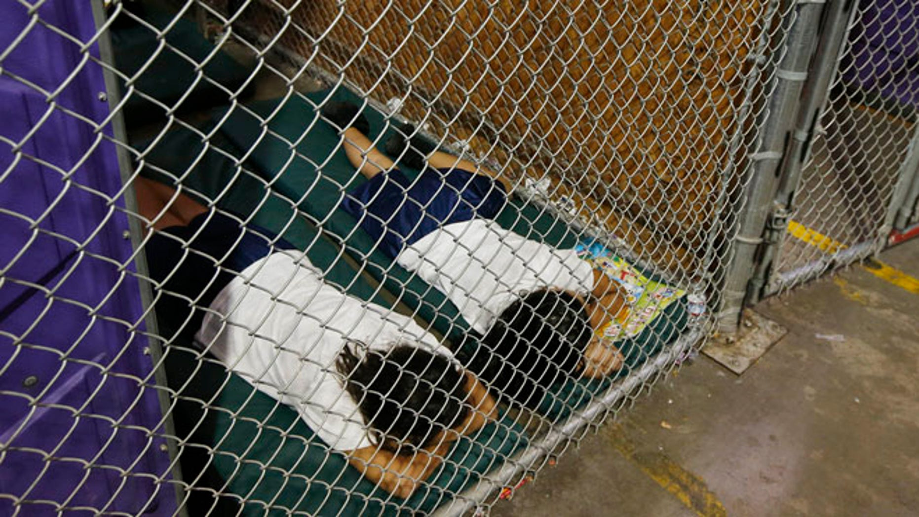 Two female detainees sleep in a holding cell, as the children are separated by age group and gender, as hundreds of mostly Central American immigrant children are being processed and held at the U.S. Customs and Border Protection (CBP) Nogales Placement Center in Nogales, Arizona, June 18, 2014.