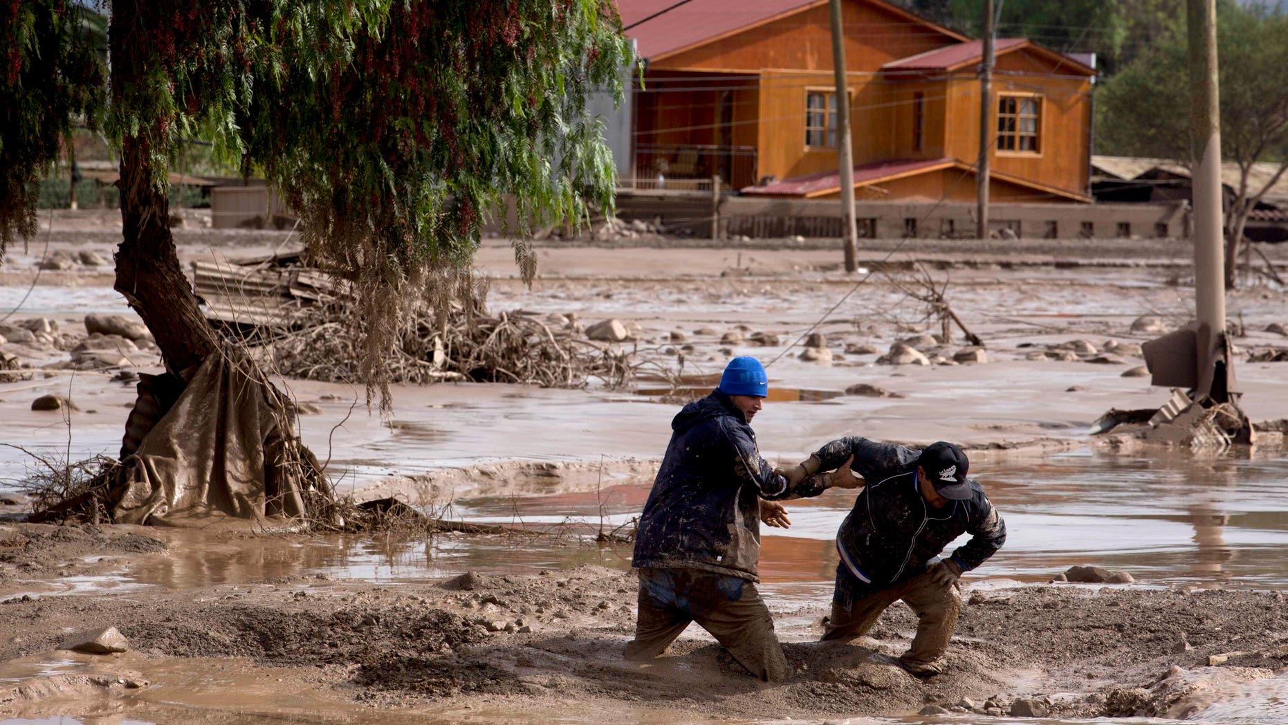 Dos hombres se ayudan entre sí a cruzar una calle cubierta en lodo en Copiapó, Chile, el jueves 26 de marzo de 2015. Inusuales tormentas y lluvias torrenciales que comenzaron el martes, han bloqueado los caminos, provocado fallas eléctricas y afectado a unas 600 personas en esta región habitualmente seca. (Foto AP/Pablo Sanhueza)