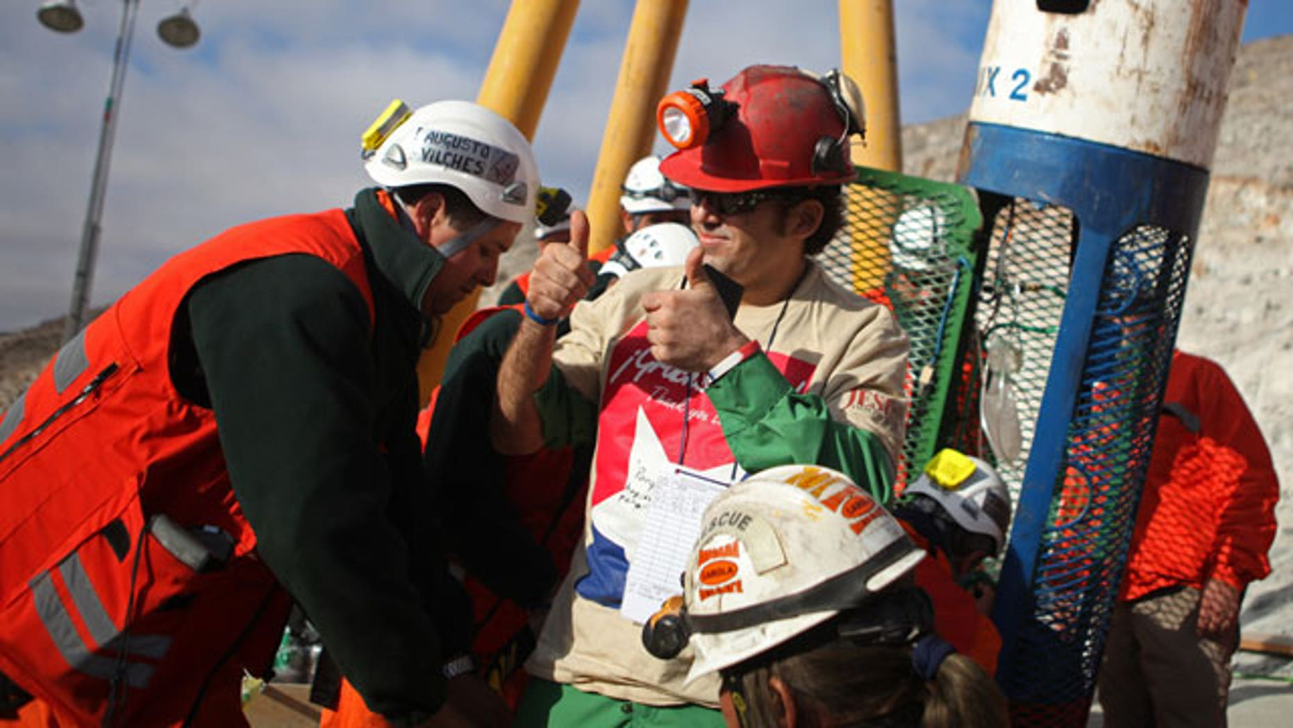 In this photo released by the Chilean government, miner Alex Vega gestures after being rescued from the collapsed San Jose gold and copper mine where he had been trapped with 32 other miners for over two months near Copiapo, Chile, Wednesday Oct. 13, 2010.