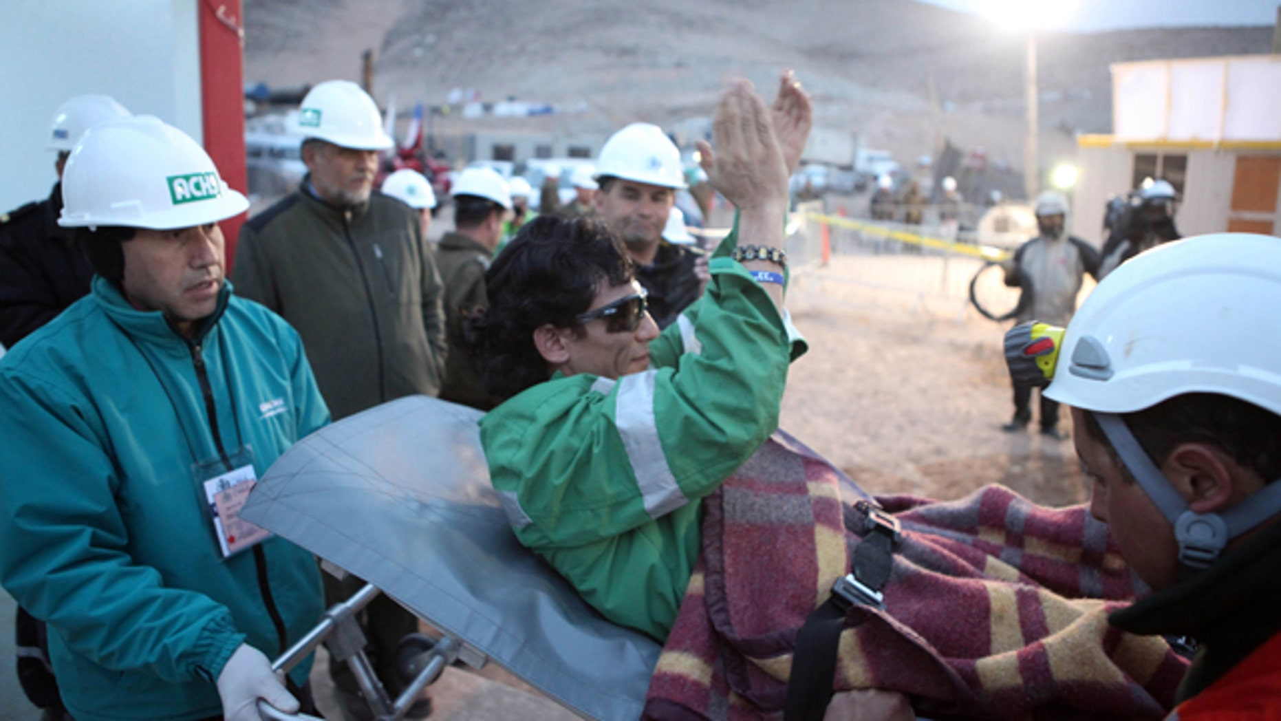 Miner Claudio Yanez celebrates as he is wheeled into a field hospital after arriving as the eighth miner to be hoisted to the surface in Copiapo October 13, 2010.