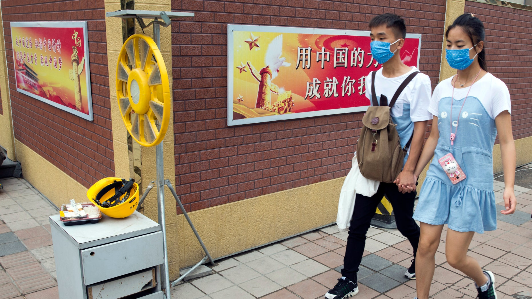 """In this Friday, July 15, 2016 photo, a Chinese couple wearing masks to protect against air pollution walk past a Chinese government propaganda slogan for the """"Chinese Dream"""" in Beijing. Beijing's notoriously awful air quality improved significantly in the first half of the year, with actions taken to curb the city's heavy pollution having a positive effect, officials in the Chinese capital said Monday, July 19, 2016. (AP Photo/Ng Han Guan)"""