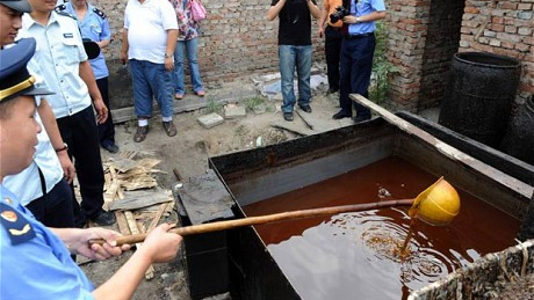 """Police inspect illegal cooking oil, better known as """"sewer oil"""" seized during a crackdown in Beijing."""