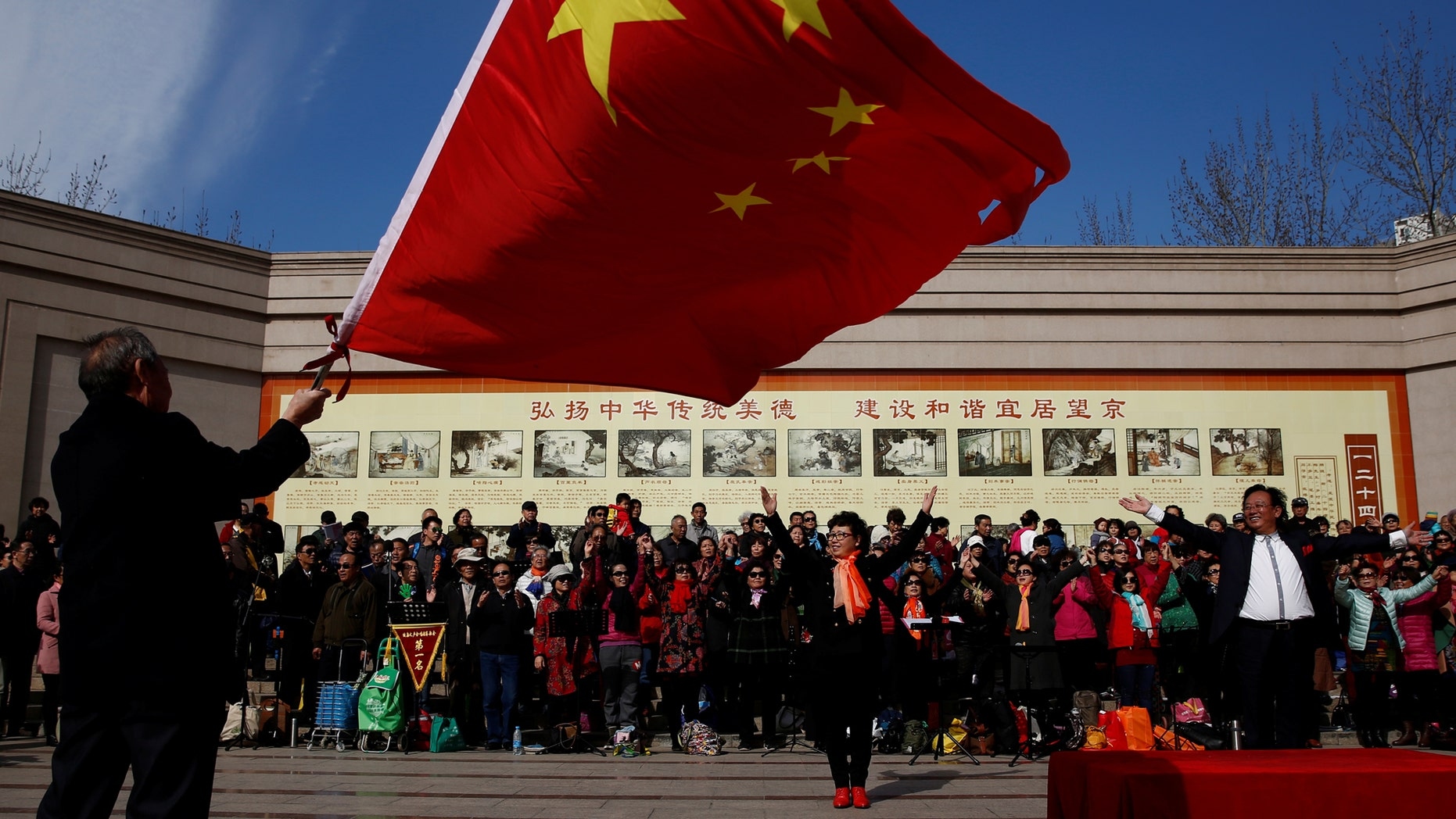 File photo: A man waves the Chinese national flag as an amateur choir performs in a park in a residential neighborhood in Beijing, China February 28, 2017. (REUTERS/Thomas Peter)