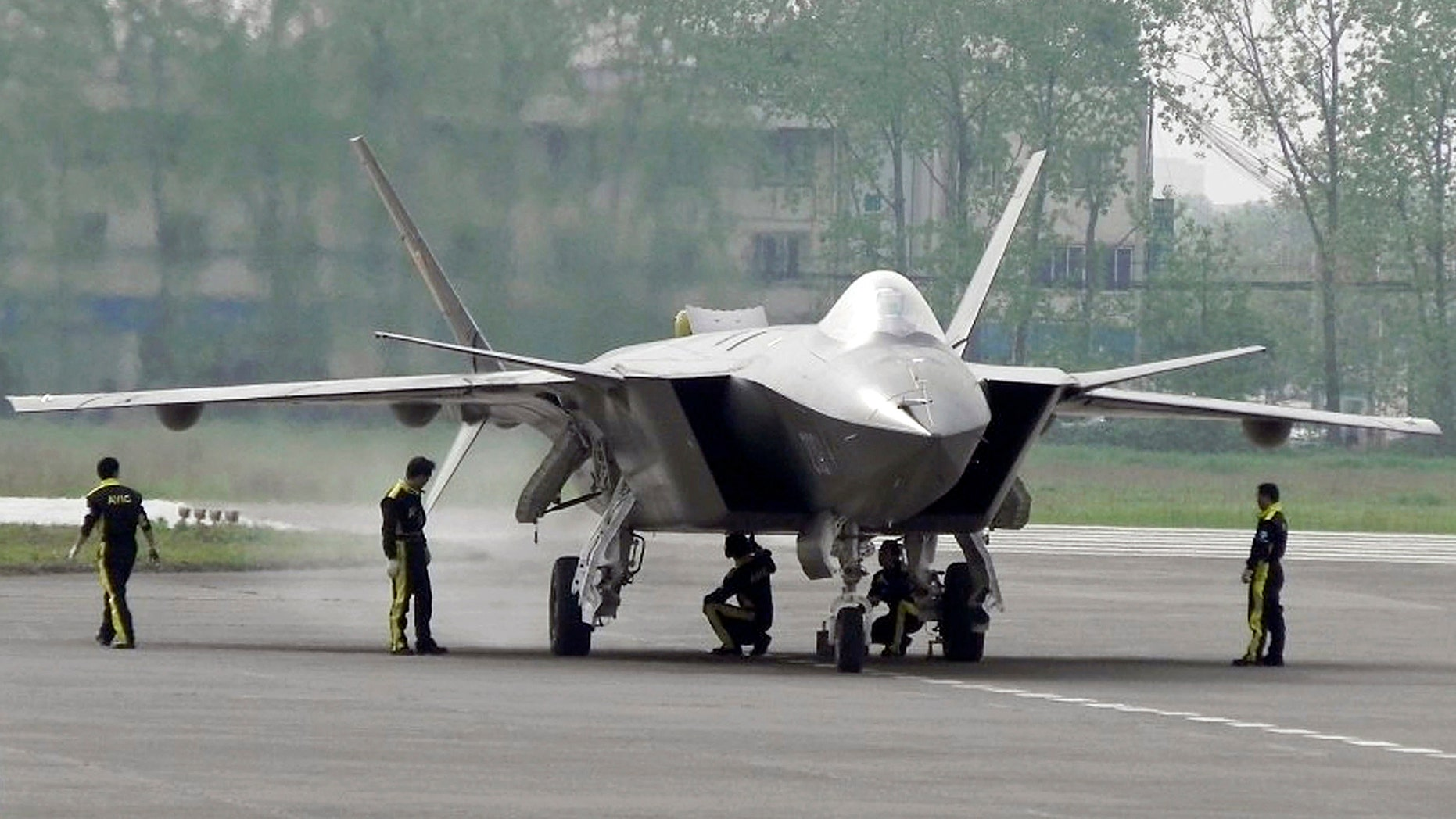 FILE - In this April 17, 2011 file photo, Chinese ground crew members inspect a J-20 stealth fighter in Chengdu, in southwest China's Sichuan province. China's defense budget will rise 8 percent to 1.1 trillion yuan ($173 billion) this year as the country is preparing to launch its second aircraft carrier, integrating stealth fighters into its air force and fielding an array of advanced missiles able to attack air and sea targets at vast distances, according to a report released Monday, March 5, 2018. (Color China Photo via AP, File)