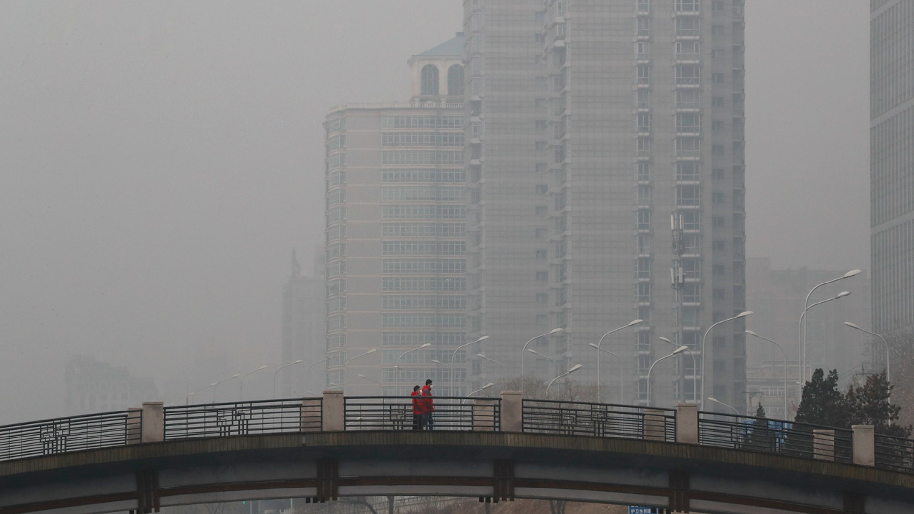 Chinese men wearing masks to filter the pollution walk on a bridge near building shrouded by fog and pollution in Beijing, Thursday, Jan. 5, 2017.