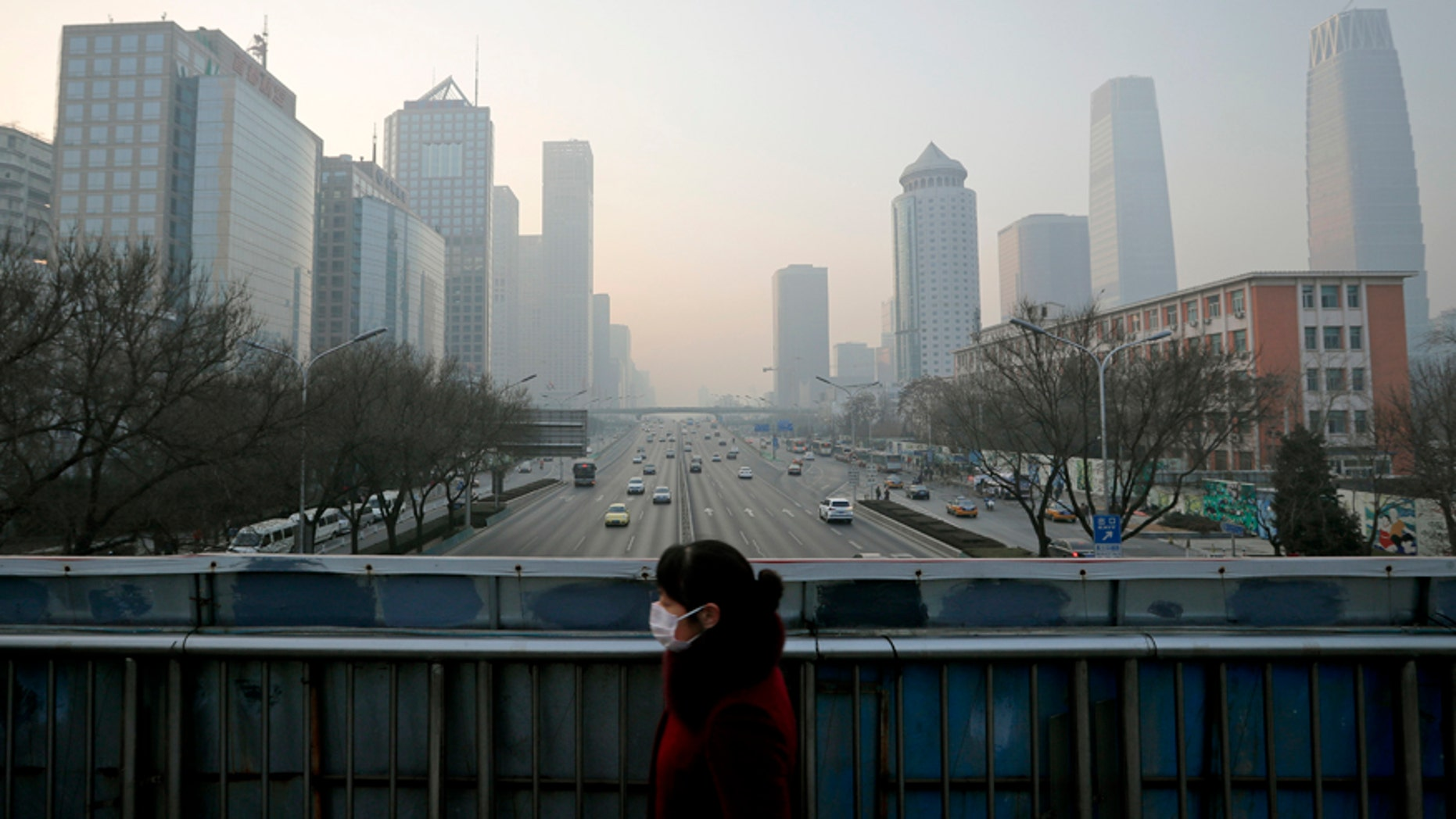 A woman wearing a mask for protection against air pollution walks on a pedestrian overhead bridge in Beijing as the capital of China is shrouded by heavy smog Monday, Dec. 19, 2016.