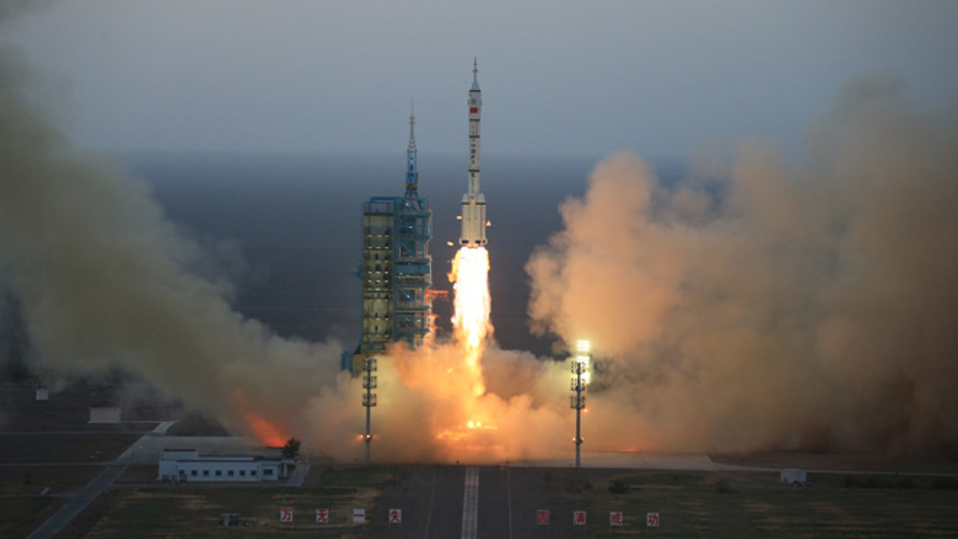 In this photo provided by China's Xinhua News Agency, the Long March-2F carrier rocket carrying China's Shenzhou 11 spacecraft blasts off from the launch pad at the Jiuquan Satellite Launch Center in Jiuquan, northwest China's Gansu Province, Monday, Oct. 17, 2016.