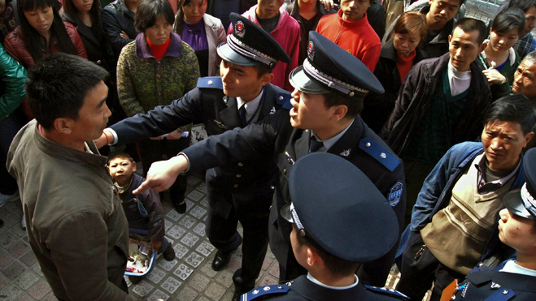 Nov. 20, 2011: Officers of the urban management bureau, known as chengguan in Chinese, demand a beggar and his child to leave a street in Guiyang, in southwestern China's Guizhou province.