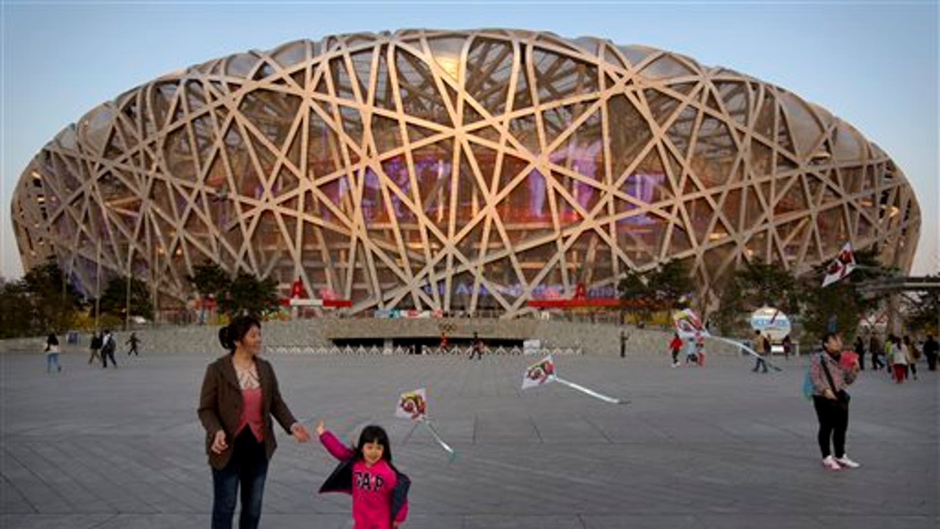 In this March 28, 2015 photo, a girl flies a kite on Olympic Green near Beijing National Stadium, also known as the Birds Nest and the site of track and field events during the 2008 Beijing Olympics, in Beijing. (AP Photo/Mark Schiefelbein)