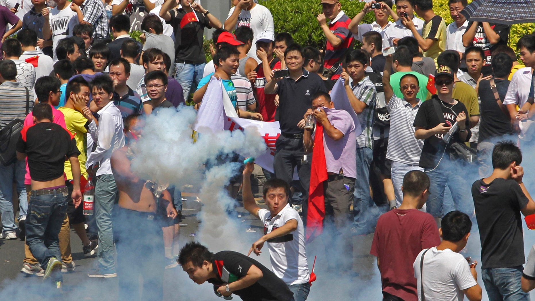 Sept. 16, 2012: A Chinese demonstrator throws a teargas canister back to riot policemen during a protest against Japan in Shenzhen, China.