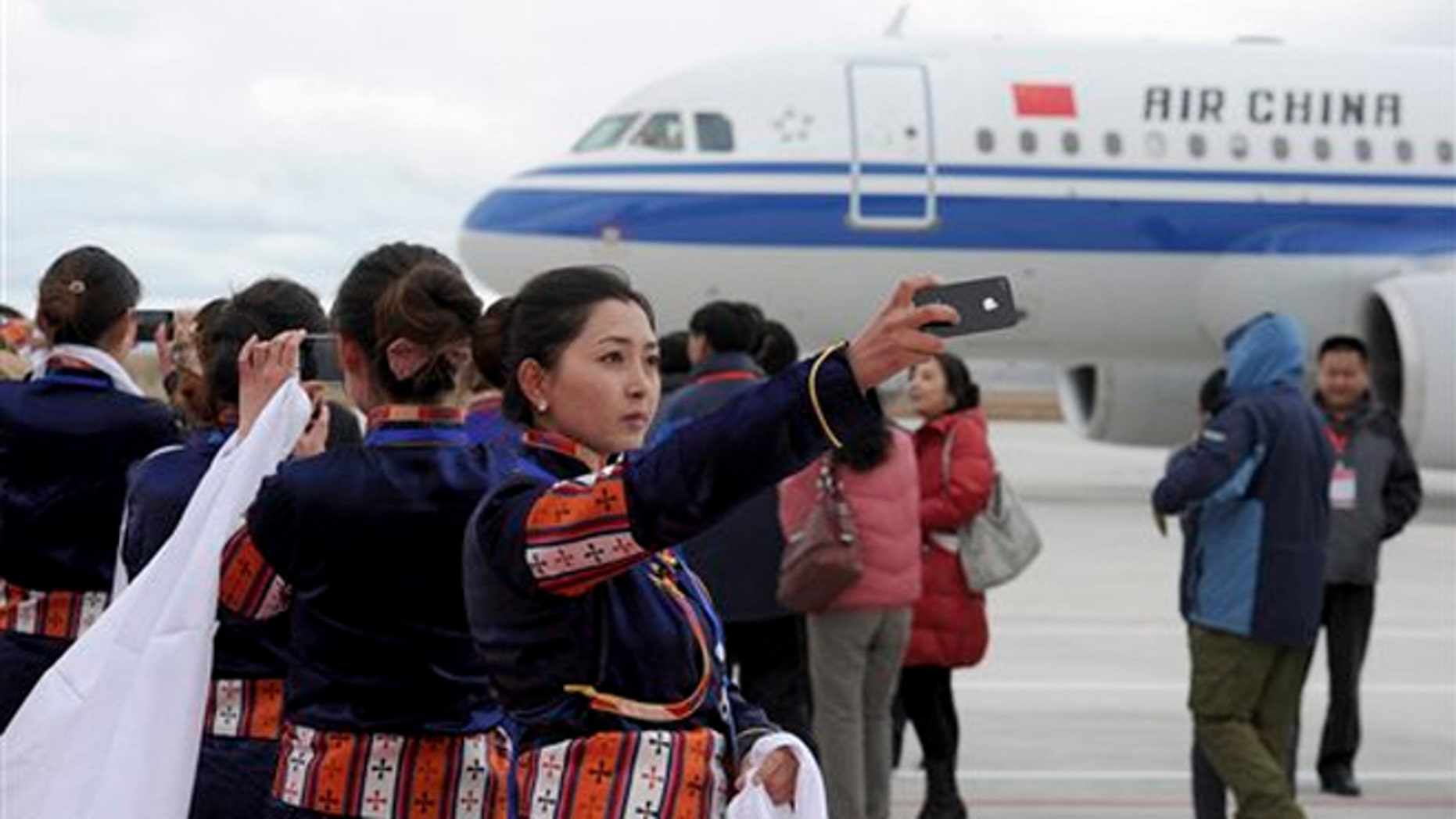 A Tibetan woman uses her cellphone to take photos of a flight that touched down at Yading airport, the world's highest-altitude civilian airport at 14,471 feet above the sea level.