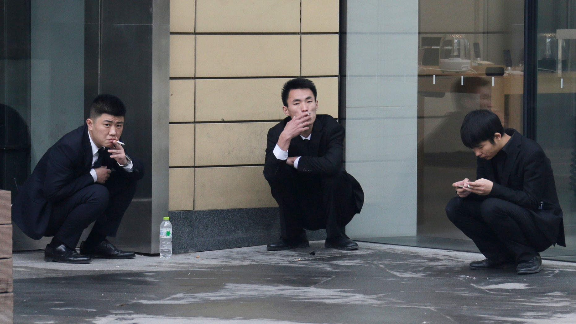 Employees smoke outside an office building in Beijing, November 25, 2014. REUTERS/Jason Lee