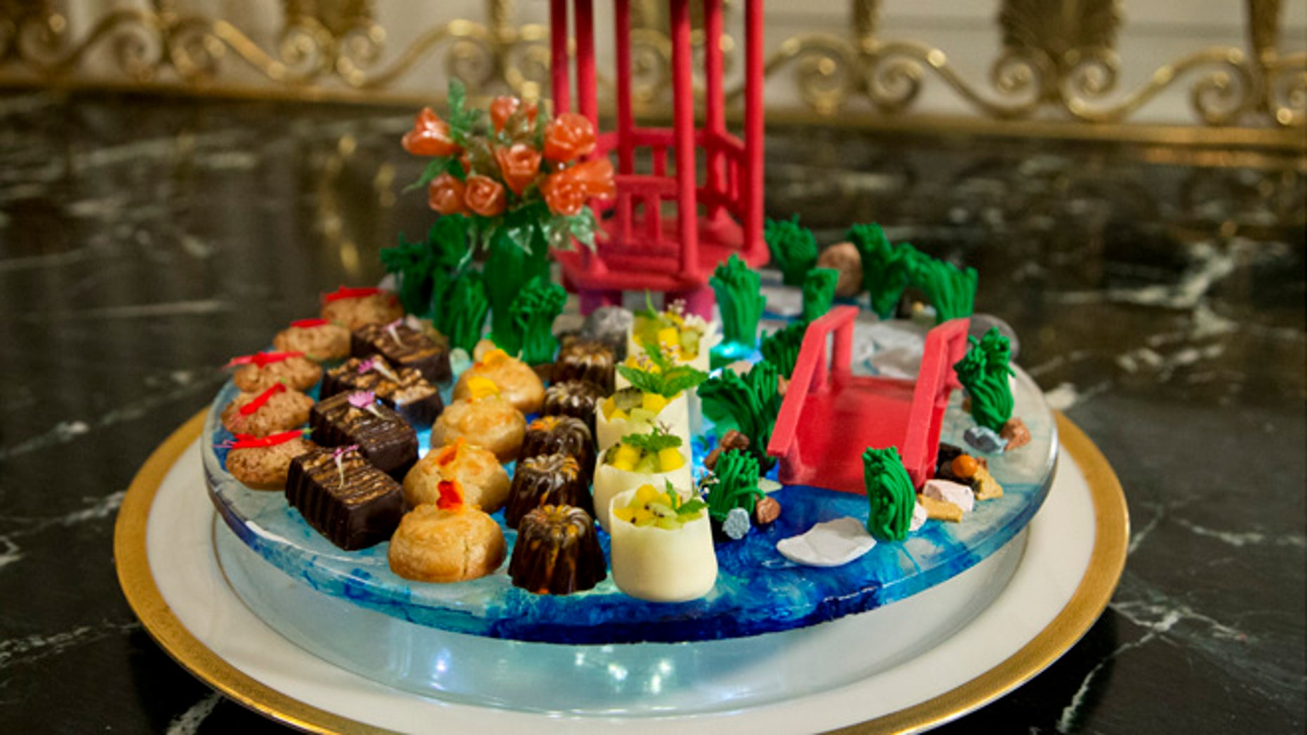 """Sept. 24, 2015: The dessert called """"a stroll through the garden"""" composed of handmade chocolate pavilion and bridge, pulled sugar roses, and white lotus flowers, that symbolize good fortune, is shown during a preview in the State Dining Room of White House in Washington for the state dinner of the visiting Chinese President Xi Jinping.(AP)"""