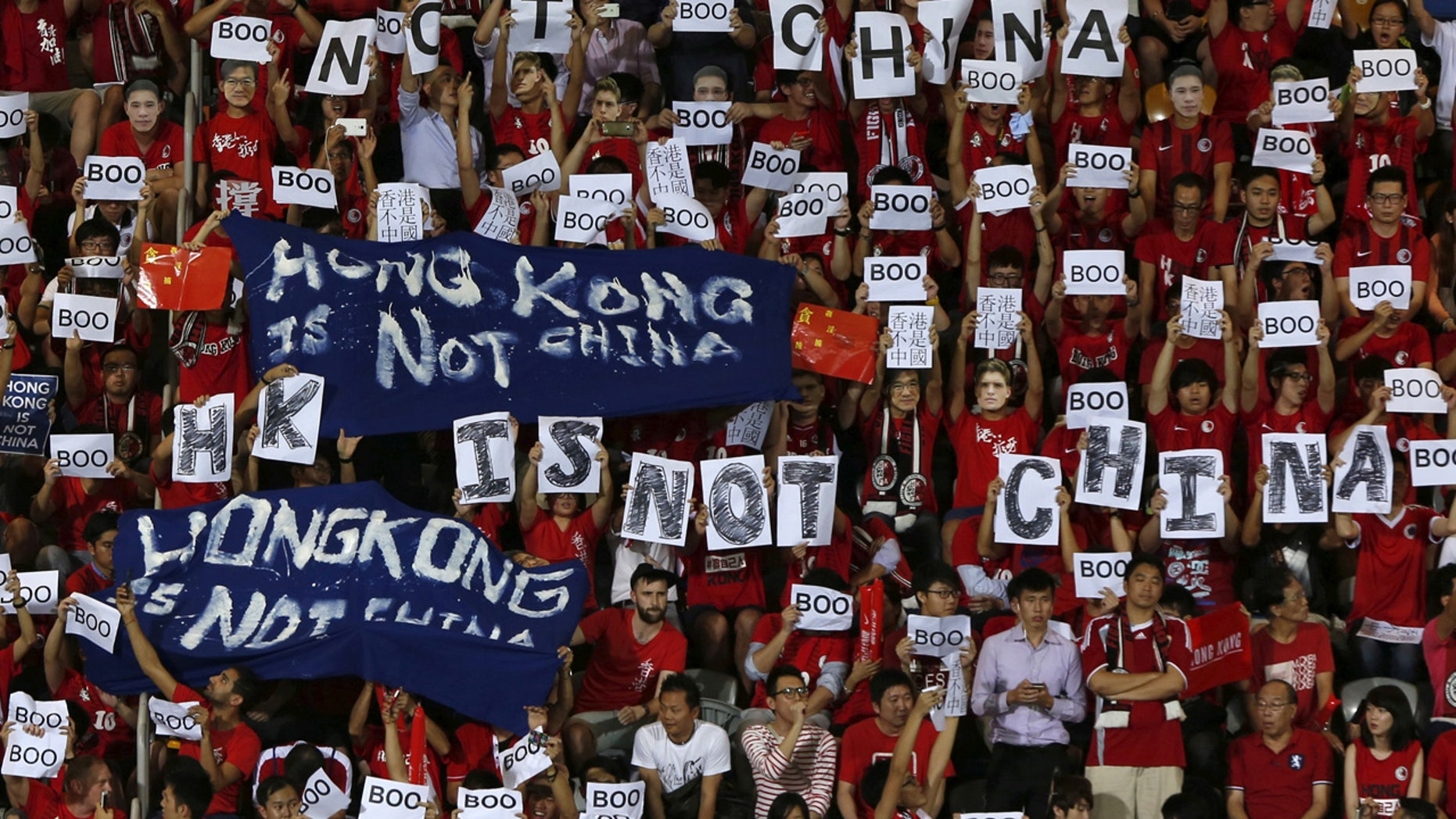 """FILE: Hong Kong fans hold banners and character signs which read """"Hong Kong is not China"""", during the 2015 World Cup qualifying match between Hong Kong and China, in Hong Kong."""