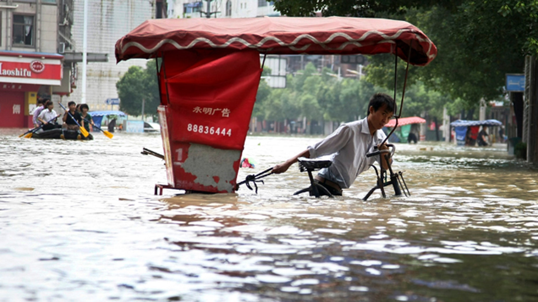 June 20: A Chinese man wades through a flooded street with his tricycle in Lanxi city in east China's Zhejiang province. Heavy rains pounded Zhejiang province over the weekend and the level of a river that passes through Lanxi city has risen sharply. (AP)