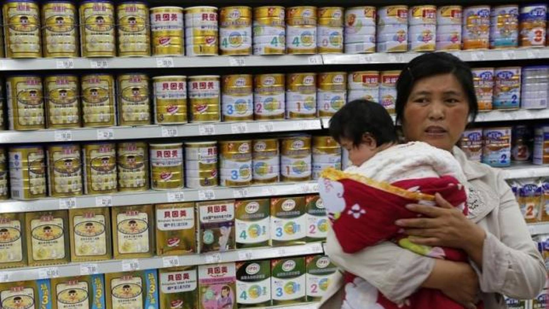 May 20, 2013: A woman holding a baby stands in front of a shelf displaying milk powder products at a supermarket in Beijing.