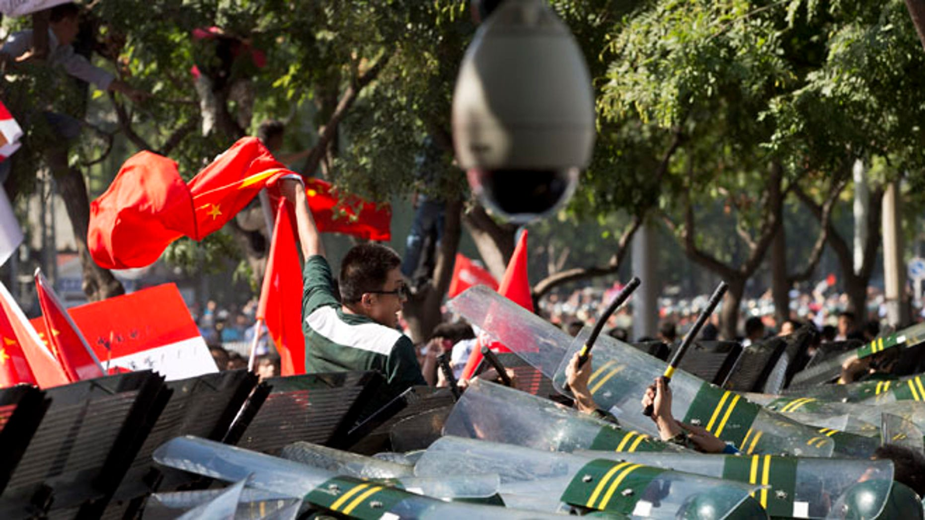 Sept. 15, 2012: A Chinese demonstrator climbs over the fence and chants slogans during an anti-Japanese protests outside the Japanese Embassy in Beijing.