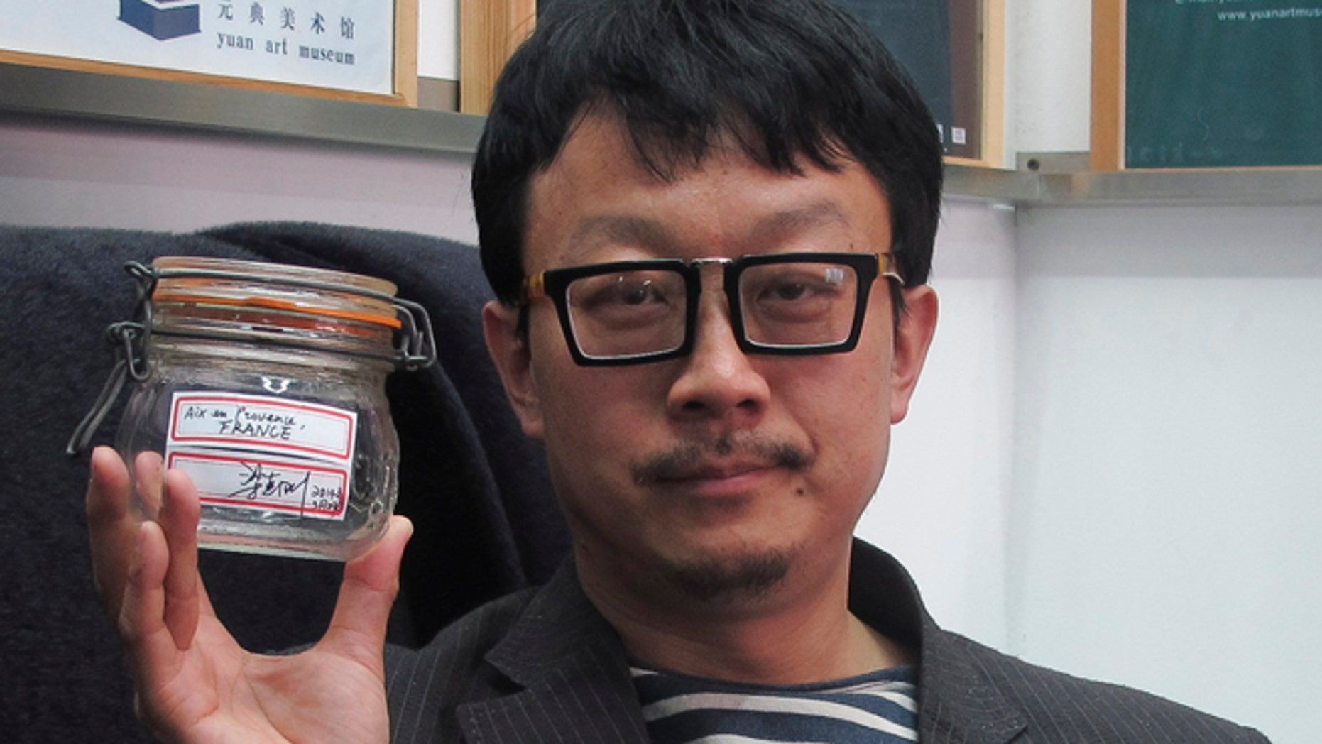 April 5, 2014: In this photo, Beijing artist Liang Kegang poses with the jar of fresh air collected in Provence, France, in an art gallery in Beijing, China.