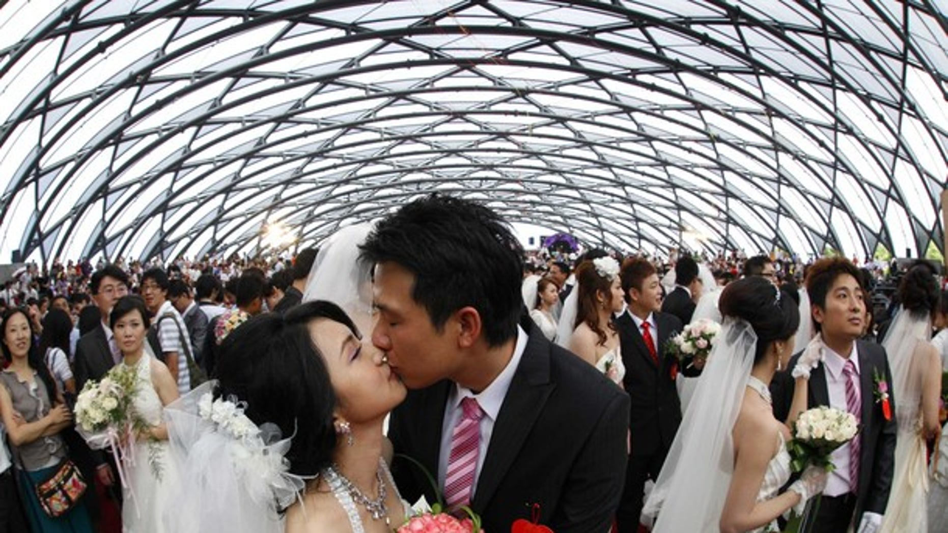 Zheng Ya-yuan (L), 32, and Chang Hong-chang, 31, who have been dating for six years, kiss during a mass wedding ceremony at the Taipei Flora Expo Hall September 9, 2010. A mass wedding ceremony was held for 163 couples on Thursday on the ninth day of the ninth month in the 99th year since the beginning of the Republic of China (Taiwan). The date which makes out to 9.9.99 is an auspicious number as the number ���9��� (pronounced jiu in Chinese) is a homophone that means lasting.  REUTERS/Nicky Loh (TAIWAN - Tags: SOCIETY IMAGES OF THE DAY)