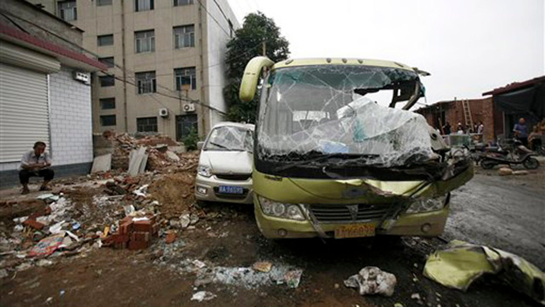 Aug. 1, 2010: Man smokes near smashed vehicles at Yuanshi county, in north China's Hebei province. A drunken shovel loader driver went on a rampage in northern China, smashing into shops and vehicles and killing 11 people, a government spokesman said Monday.