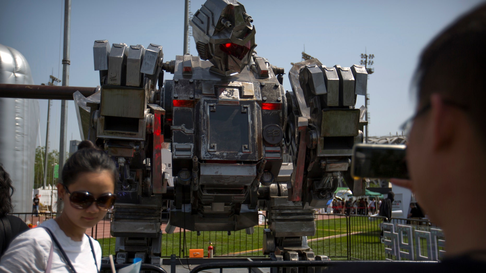 Visitors look at a giant robot named The Monkey King at the G Festival, part of the Global Mobile Internet Conference (GMIC) in Beijing, Saturday, April 29, 2017. The GMIC features current and future trends in the mobile Internet industry by some major foreign and Chinese internet companies. (AP Photo/Mark Schiefelbein)