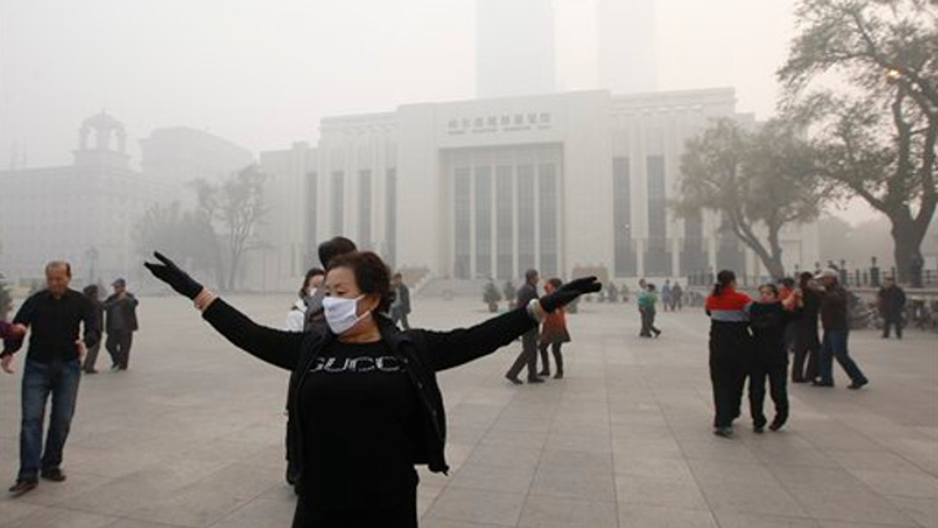 Oct. 21, 2013:  A Chinese woman wears a mask as she takes part in communal dancing during a day of heavy pollution in Harbin in northeast China's Heilongjiang province.