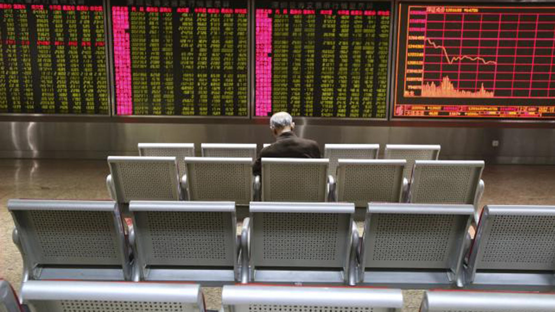 Jan. 4, 2016: An investor sits in front of a display board showing stock information at a brokerage house in Beijing. (Reuters/Li Sanxian)